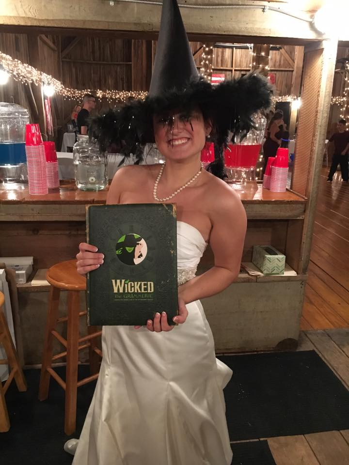 A bride wearing a wicked witch hat and holding a book from the Musical Wicked