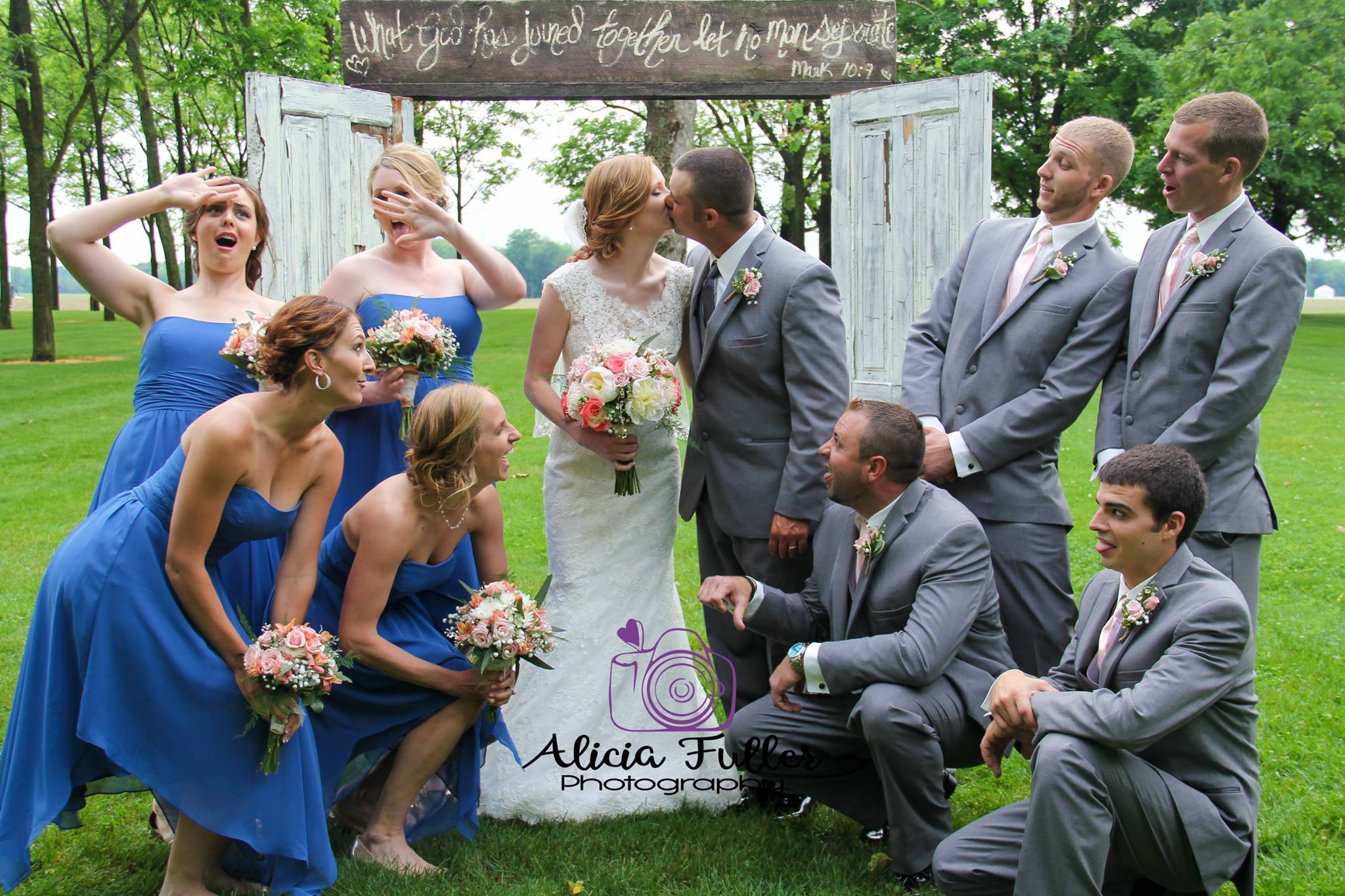 A funny pose by the Bride, Groom & Bridal Party in from of rustic doors