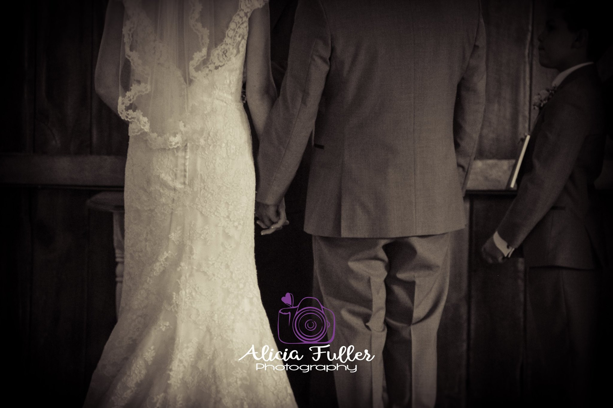 A Black and white picture of a Bride & Groom standing at the altar