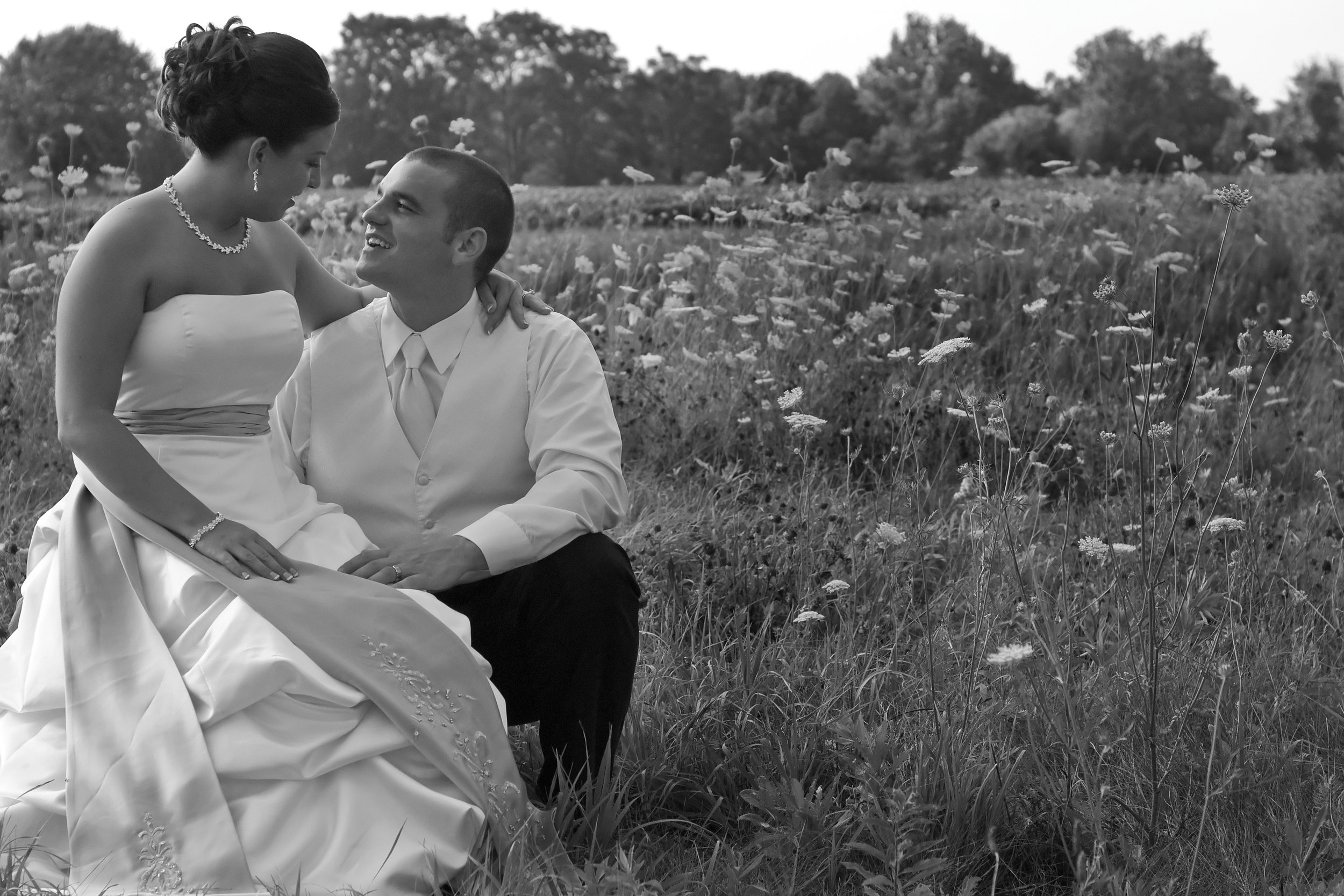 A Bride sitting on her groom's knee gazing into his face in a field