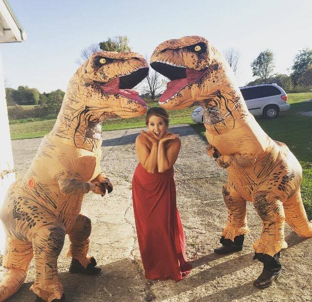 A Bridesmaid with 2 blowup dinosaurs.  A Bridesmaid in trouble