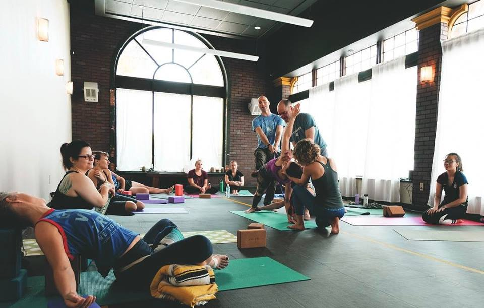 """Dr. Sarah Sue Myers assists in holding the cranium during a class at  We Yoga Co  in Seattle, WA.  """"""""Sometimes it takes a village... or a COmmunity."""" - We Yoga Co. on Facebook"""