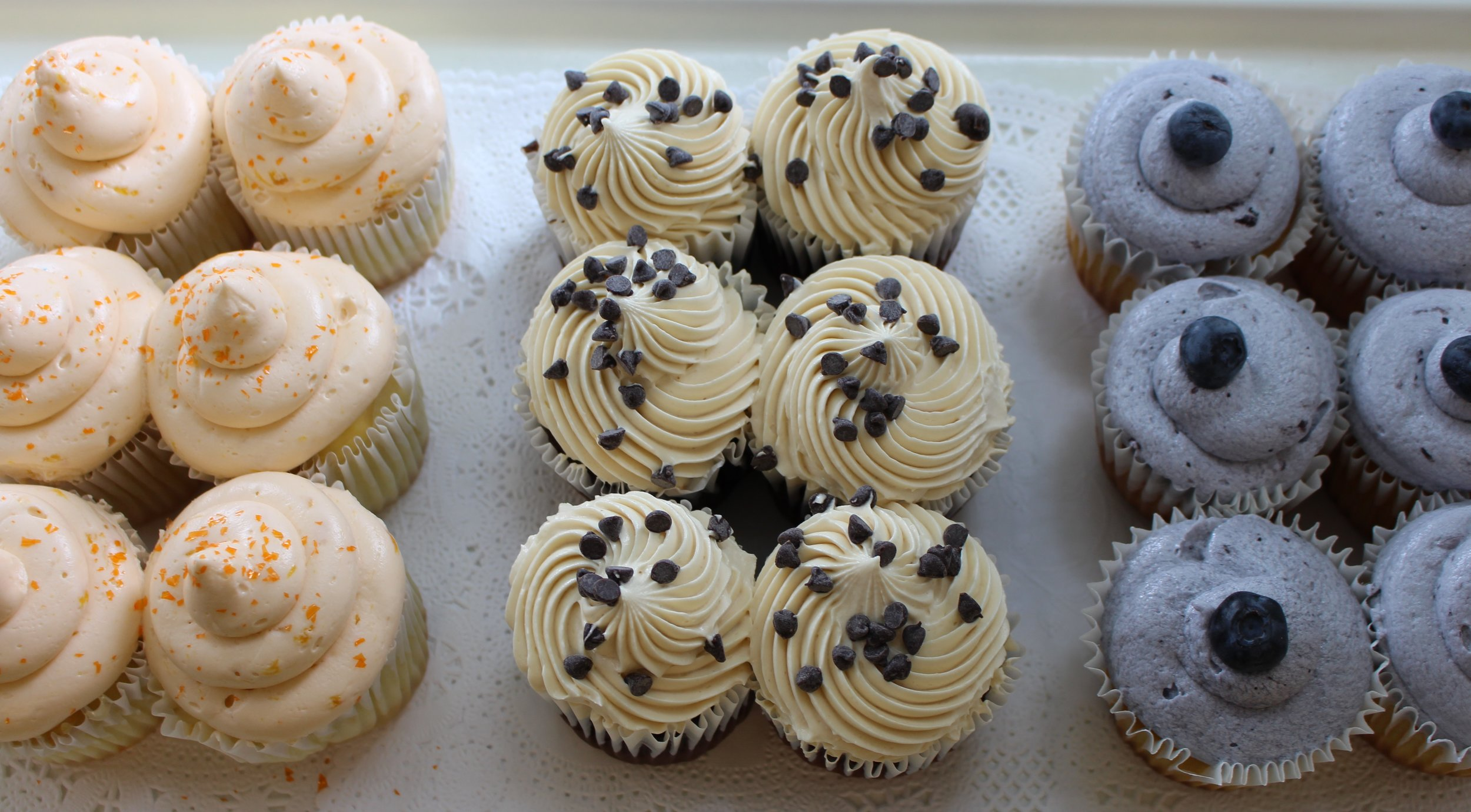 Assorted cupcakes from our cupcake bar. Cupcakes shown include peach, chocolate peanut butter, and blueberry