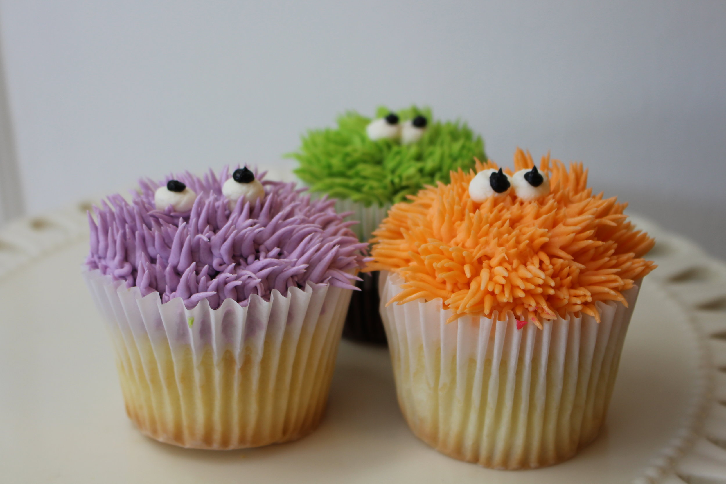 Monster decorated cupcakes with chocolate or white cake, furry colors and peering eyes