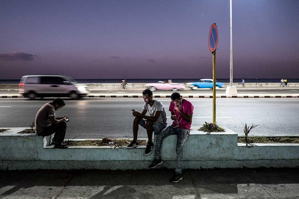 Youth surf the web alongside of Malecón highway in Havana, Cuba. © Moe Zoyari