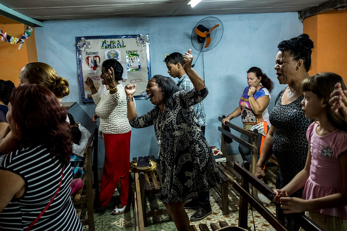 People dance and sing while they pray in a church in Havana, Cuba.