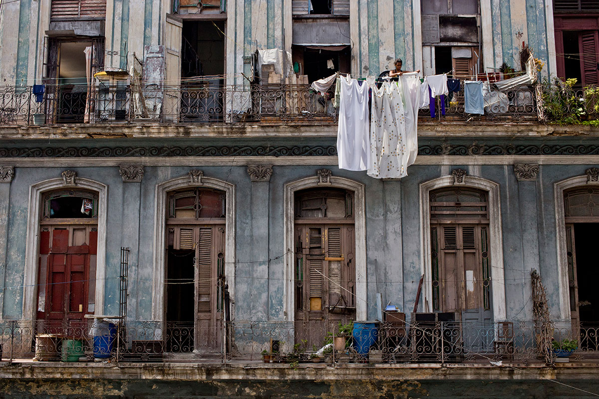 A woman hangs bed sheets to dry in Havana, Cuba.