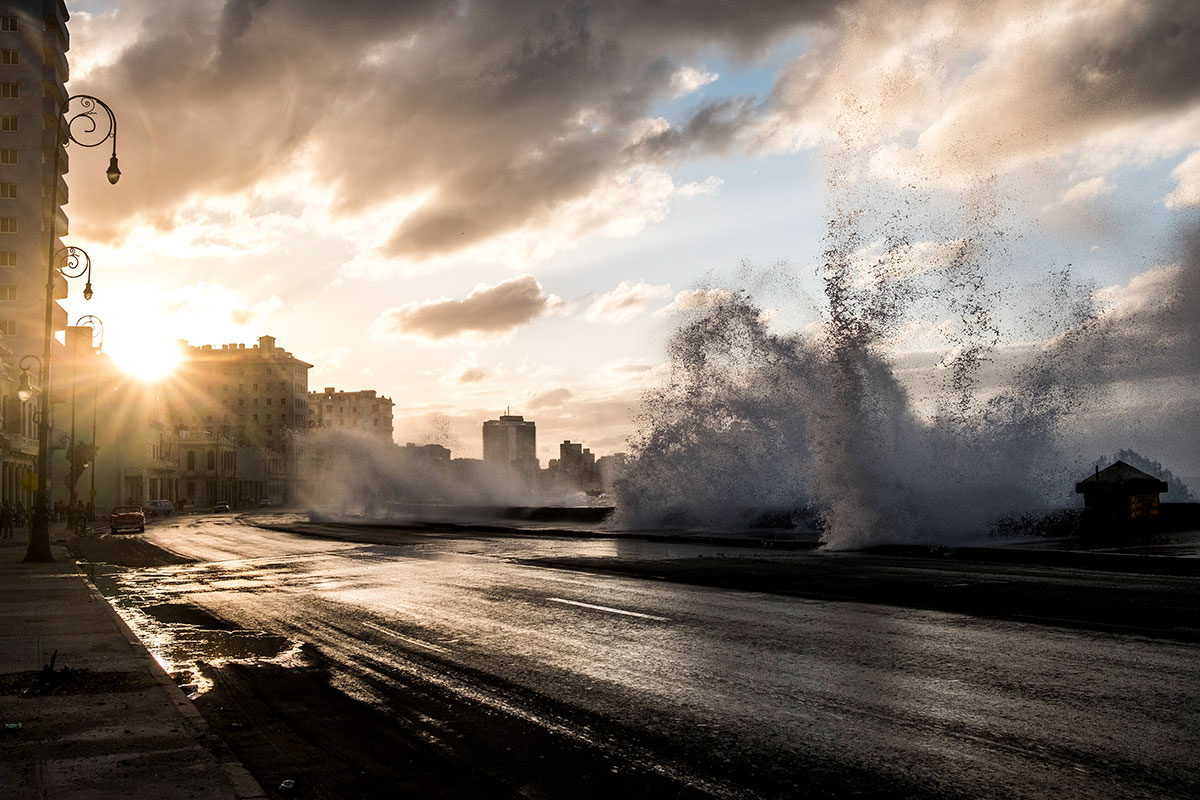 Waves crash over the Malecon highway as sun sets in Havana, Cuba.