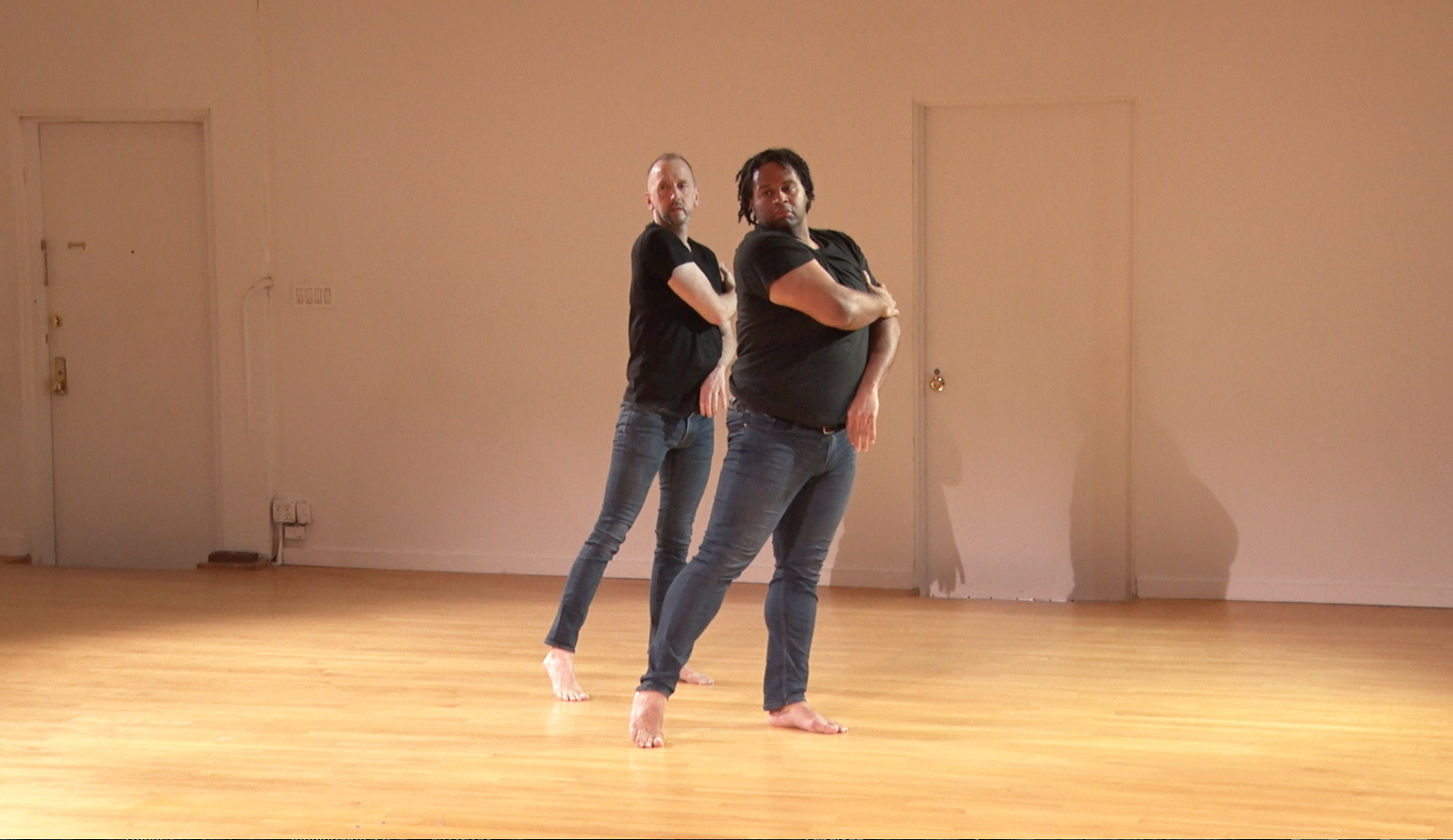 DeAngelo dancing with John Jasperse. Photo still from video by Davidson Gliotti.