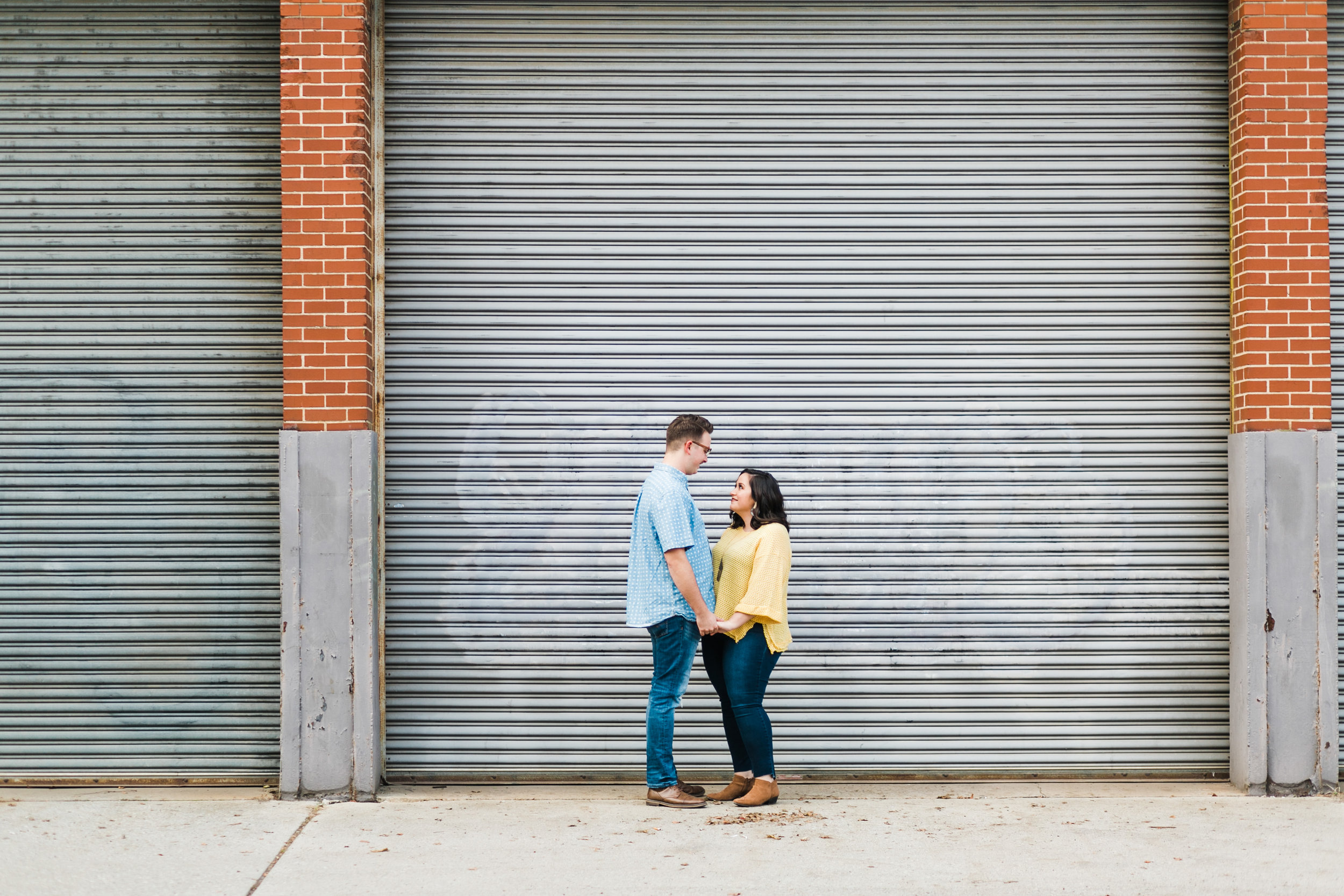 couple standing in front of bay doors engagement session