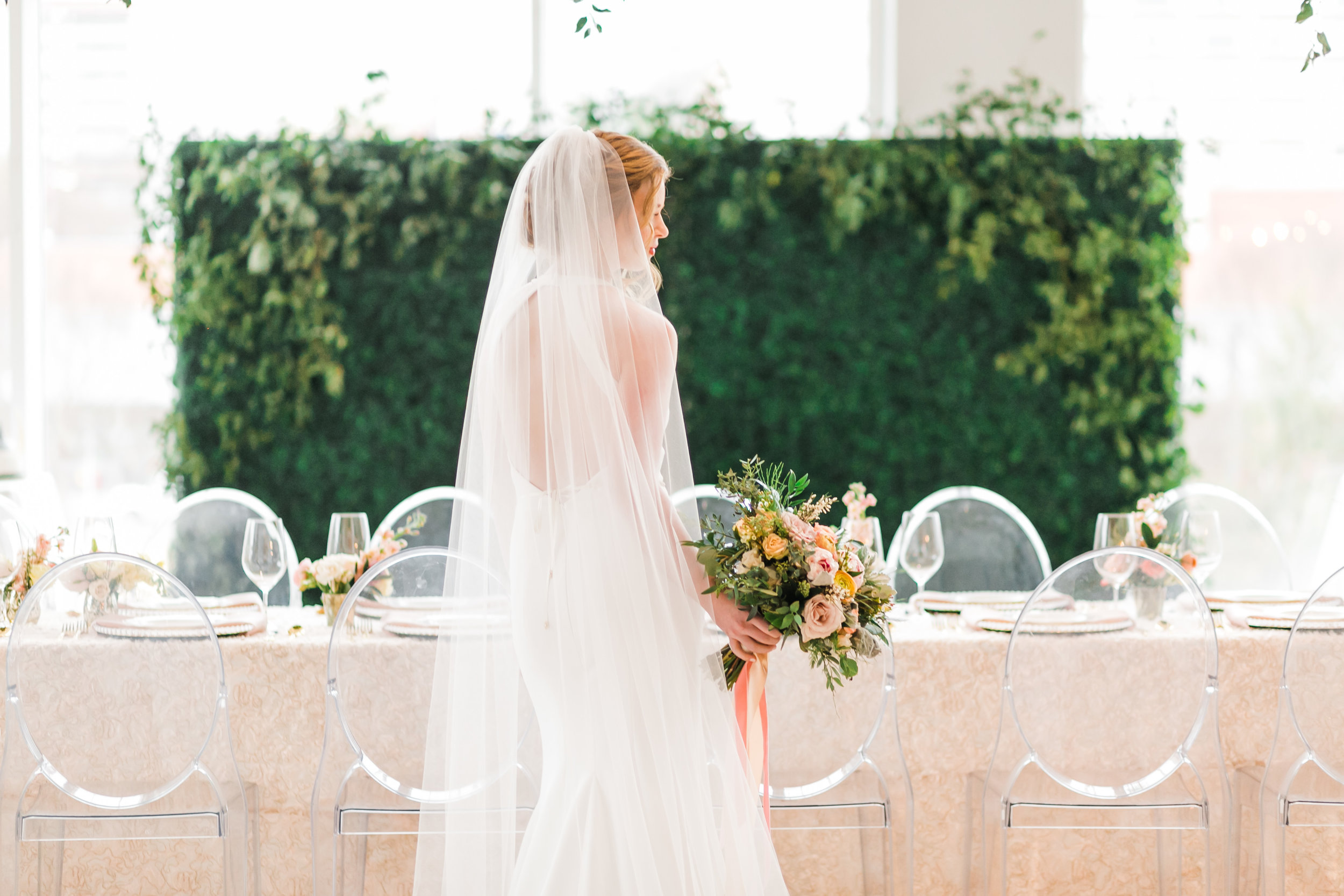 bride in front of reception table with greenery wall indoor