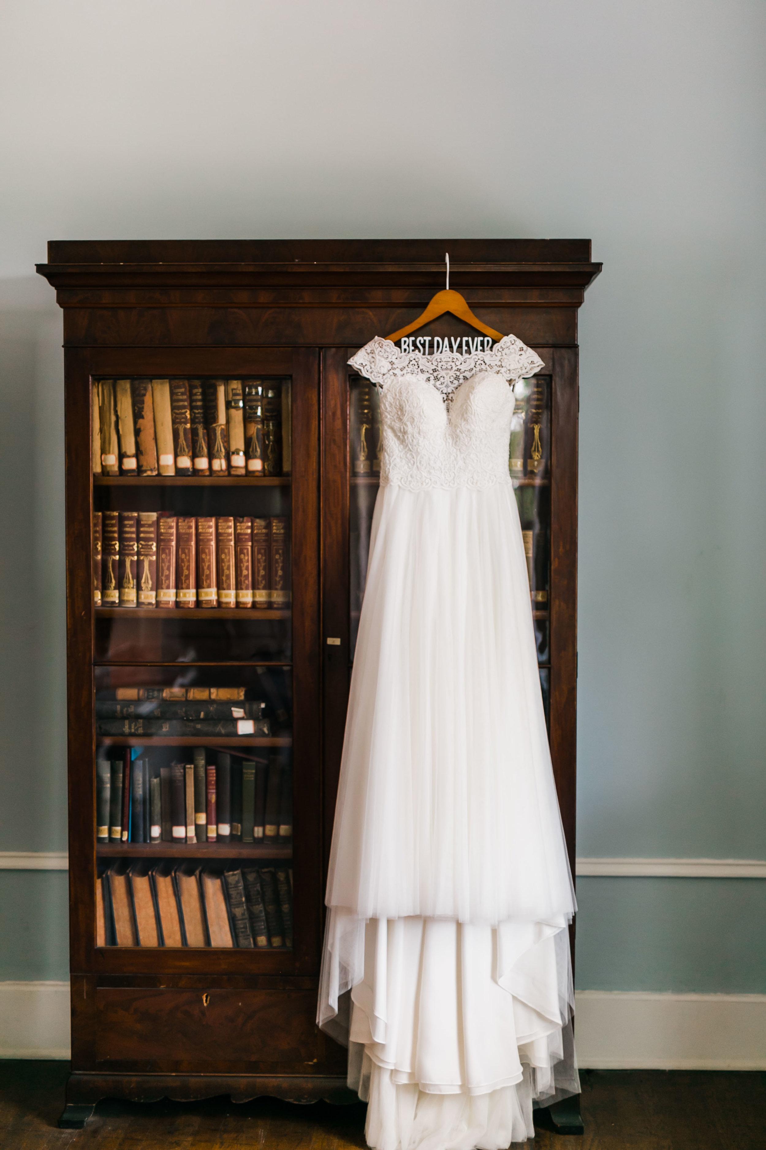 flowy wedding dress on best day ever hanger hanging on bookcase in historic bleak house