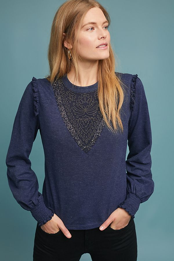 Wearing an embellishment on your shoulders draws the attention towards your face instead of your midsection. - I love this fun ruffle and bead one from Anthropologie… you can find it here.