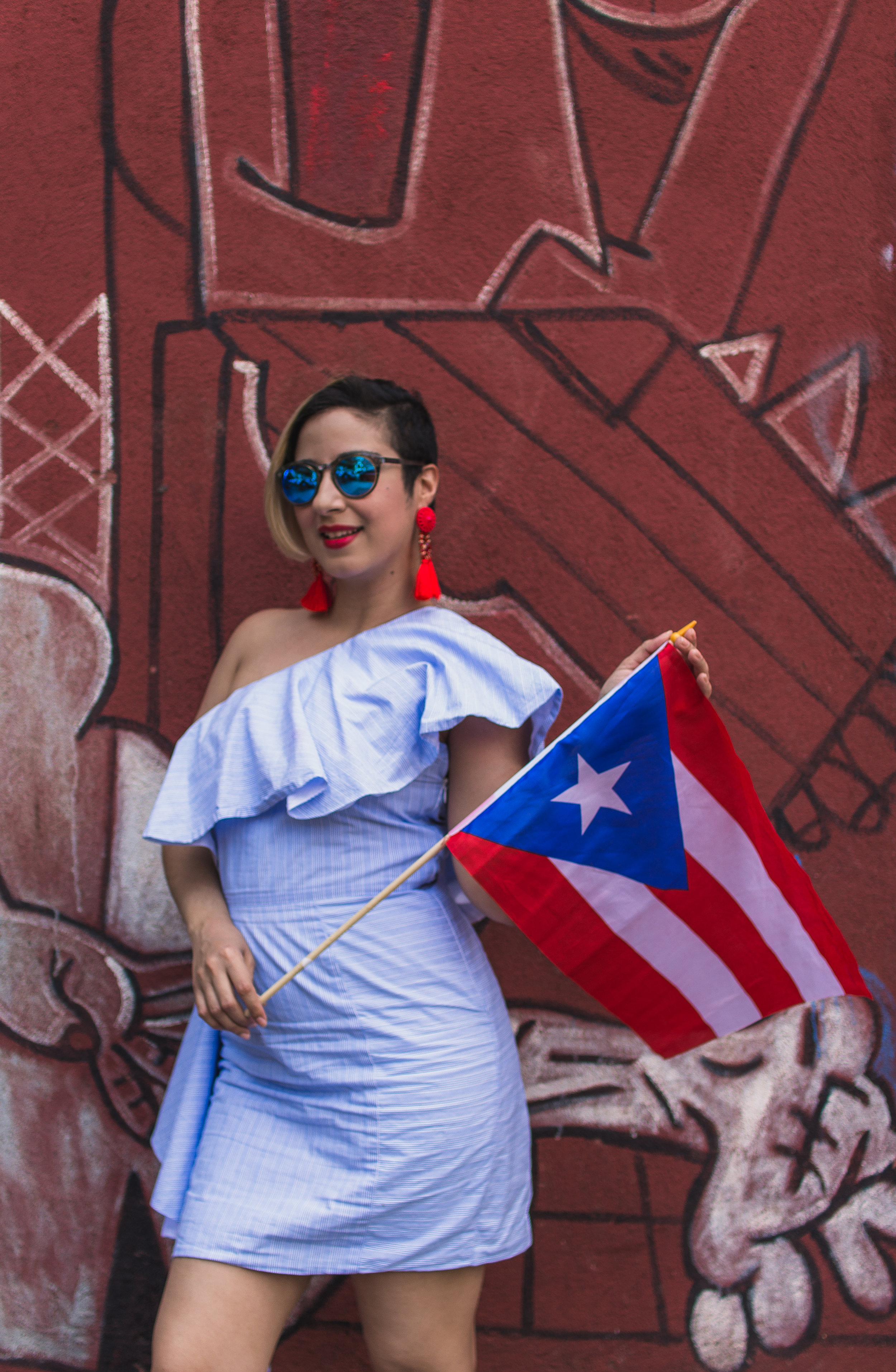 "For us  Nu yoricans, the 116th Street Festival officially sets off the Summer! It is held the second Saturday in June, and gets us all charged up for the Puerto Rican day Parade that takes place the next day! This celebration of Puerto Rican culture is not just limited to Puerto Ricans. People from all Latino and non Latino cultures gather here for a day of Music, authentic Puerto Rican cuisine, art and shopping! Spanning 20+ blocks, this grand Uptown ""Block Party"" has been going down since 1985 and is the biggest Latin Festival in the North East. You can only imagine all the walking one must do! My favorite are the two huge musical stages that are assembled on 112th street and 106th street with celebrity appearances and performances from some of the best Puerto Rican talent from old school to new school. There's a lot to do and see in between so you want to make sure your attire is adequate for roaming around on foot especially in the hot weather!   Street Festival wear has to be easy and comfortable so you are able to move around with ease. My look for the Festival this year was a playful take on the traditional Bomba y Plena dresses worn by the women who dance to these two classic musical styles from Puerto Rico. BOMBA attire is considered to be more conservative than PLENA , and this VIVA AVIVA dress is a little of both. It's definitely not conservative, BUT, the sleeveless one shoulder design is similar to the tops you see on a PLENA dress and the whimsy side ruffles mimic the ruffles in the skirts on both BOMBA and PLENA skirts. The skirts are a big part of the dances and are swished around just like the women in the Sugar Plantations used to do, which is where BOMBA originated in the 17th century. PLENA music was developed from BOMBA and was introduced in the beginning of the 20th century. I didn't use my side ruffles to dance, but I did use them to strike a pose or two! I wanted to wear Red, White and Blue to honor the colors of the Flag so the dress represents the Blue. It's not the exact Blue of the Flag but it's the kind of Blue you want to wear on an 80 degree day; light and fresh! I didn't want to be too literal, but I still wanted to represent! Red statement earrings and simple white sneakers complete the trifecta of colors that make up our beautiful flag.   I always look forward to ""Puerto Rican weekend"" in NYC. Puerto Rican Pride is contagious and you can't help but feel it in the air that weekend. The cheerful energy of the people, the Salsa you hear blasting on every street corner, the colors of the Flag freely dancing in the wind, the Savory scents of Lechon {Roast Pork} and Puerto Rican fritter dishes like Alcapurrias and Bacalaitos in the air, the chanting of the people screaming ""Yo soy BORICUA, pa' que tu lo sepas!""  all contribute to the Magic of the 116th Festival.   A huge thank you to LEAH & CAV for coming all the way from Queens to spend the afternoon in EL BARRIO with me! They were so much fun to work with and made me feel super comfortable! Remember Fashionistas! Dress to the beat of your own drum, even if it goes against what everyone else is doing!  With Style & Pizazz,  YAZ  Photographer: Leah Santos (Instagram @Theneolang  Videographer: Cav (Instagram @dreamers.revenge)      Dress: VIVA AVIVA - Renttherunway.com  Earrings & Sneakers: Amazon.com"