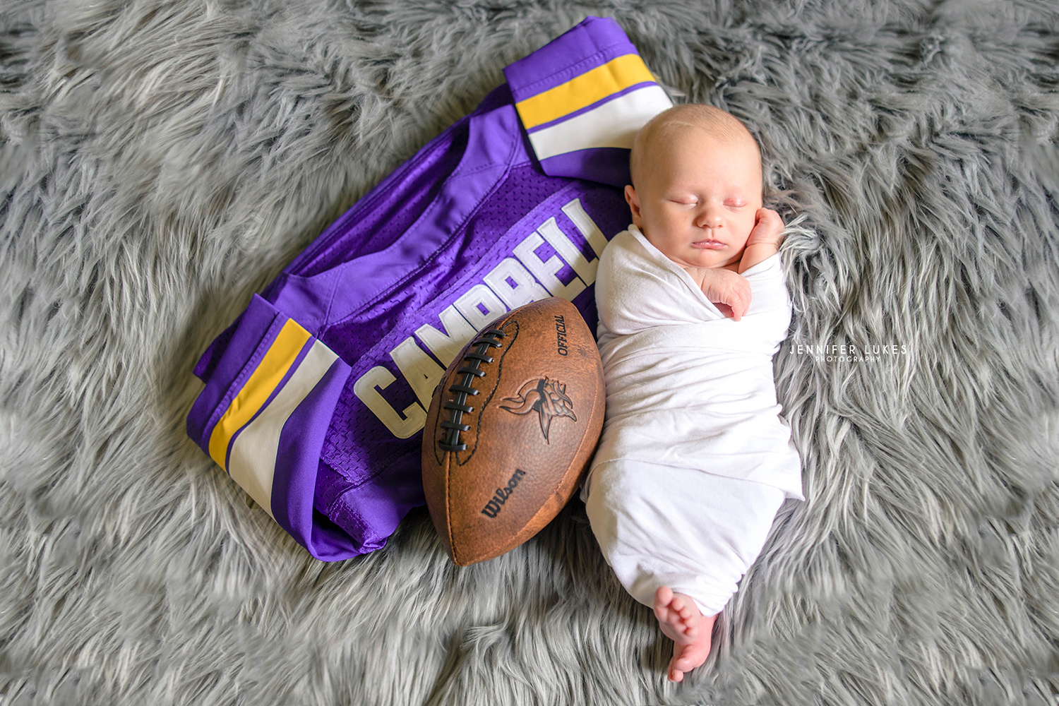 Sammamish in-home photo session of newborn with football and jersey.