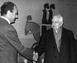 Un ormai anziano De Chirico stringe la mano a Thellung, presso la sua mostra personale.