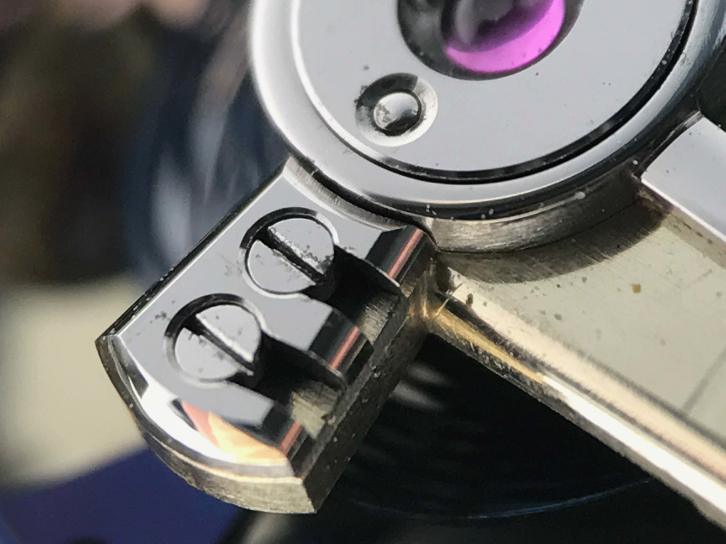 Stud holding the balance spring, the direction of the screws is irregular to the majoroty of watches with a similar system.