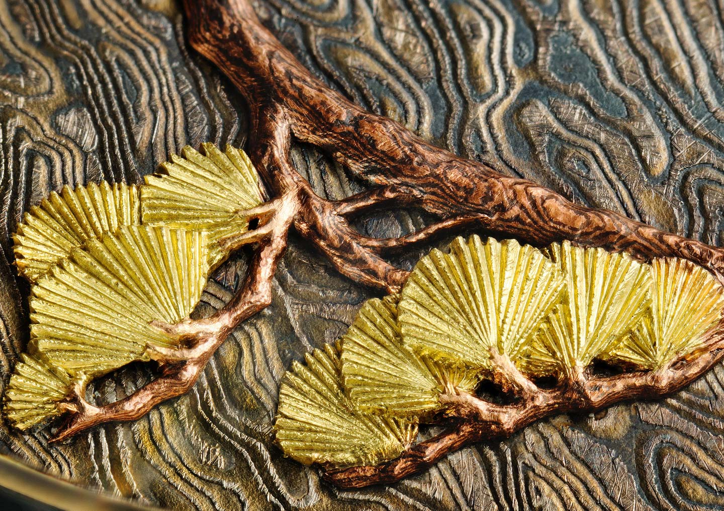 The branch is made of  mokume gane  of pink gold/ shakudo .The leaves are in green gold .  (Image by Guy Lucas de Peslouan).