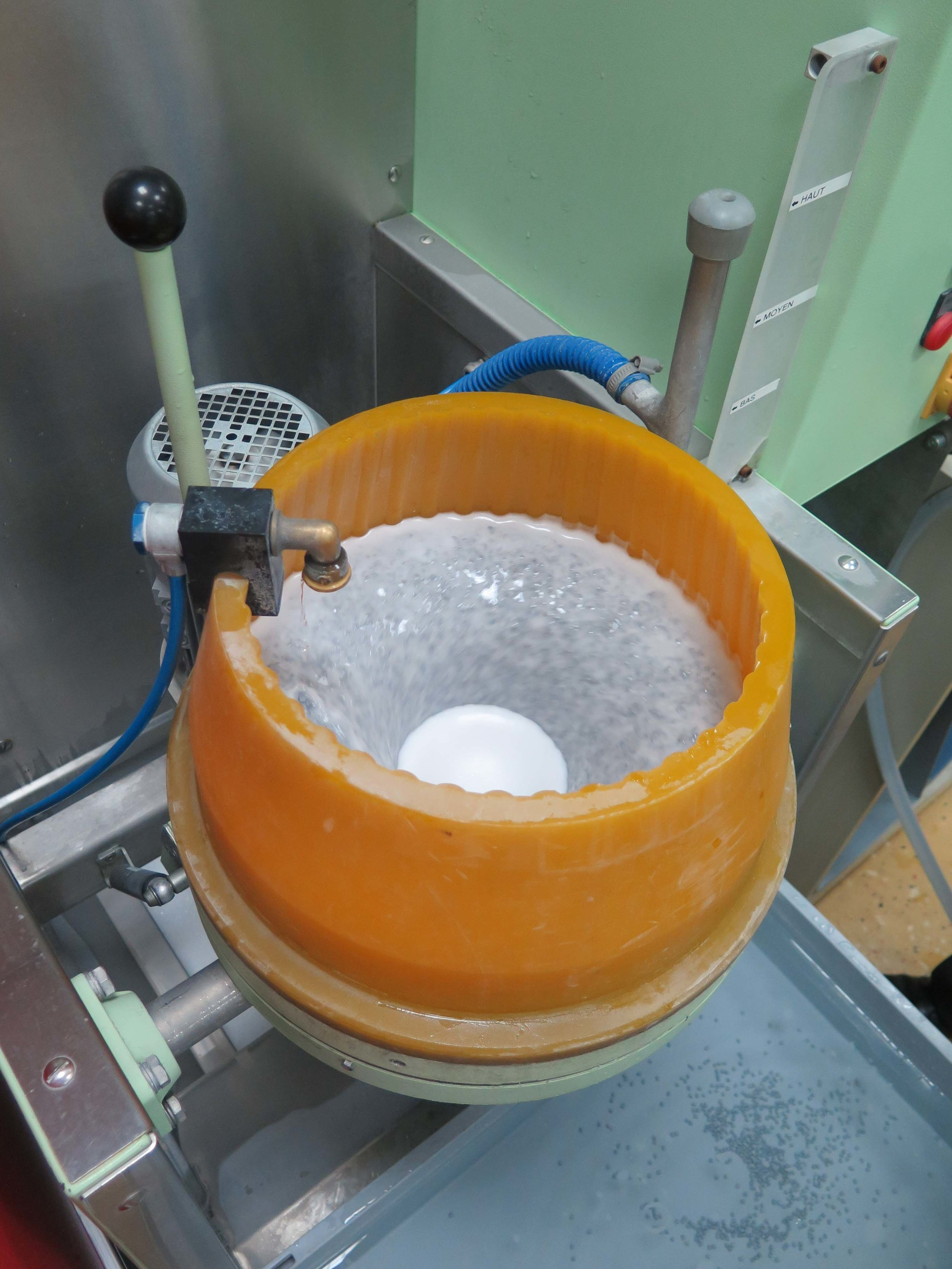 The tumbler turning the pieces to be treated with the ceramic beads in water
