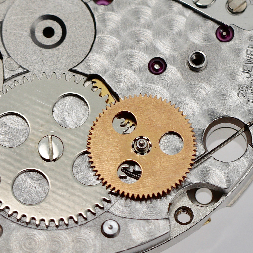 The central wheel is driven by the reverser block and drives the ratchet wheel.