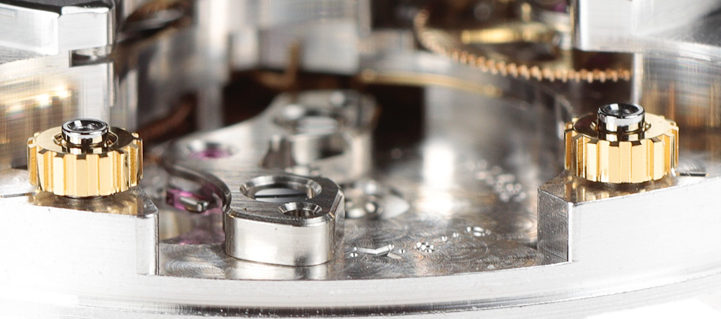 The threaded spacers can be adjusted up/down, altering the position of the balance bridge to allow the end-shake of the balance staff to be easily and precisely adjusted. A similar system to that used by Rolex on their recent calibres.