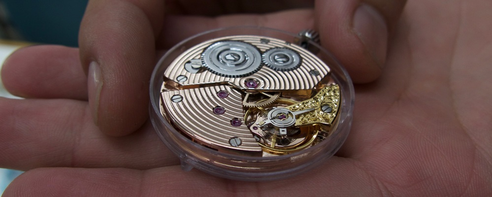 The barrel and train bridges have been decorated using a circular Geneva stripe finish, then plated in red gold. The balance cock is hand engraved, also hand angled and yellow gold plated to match the balance wheel .