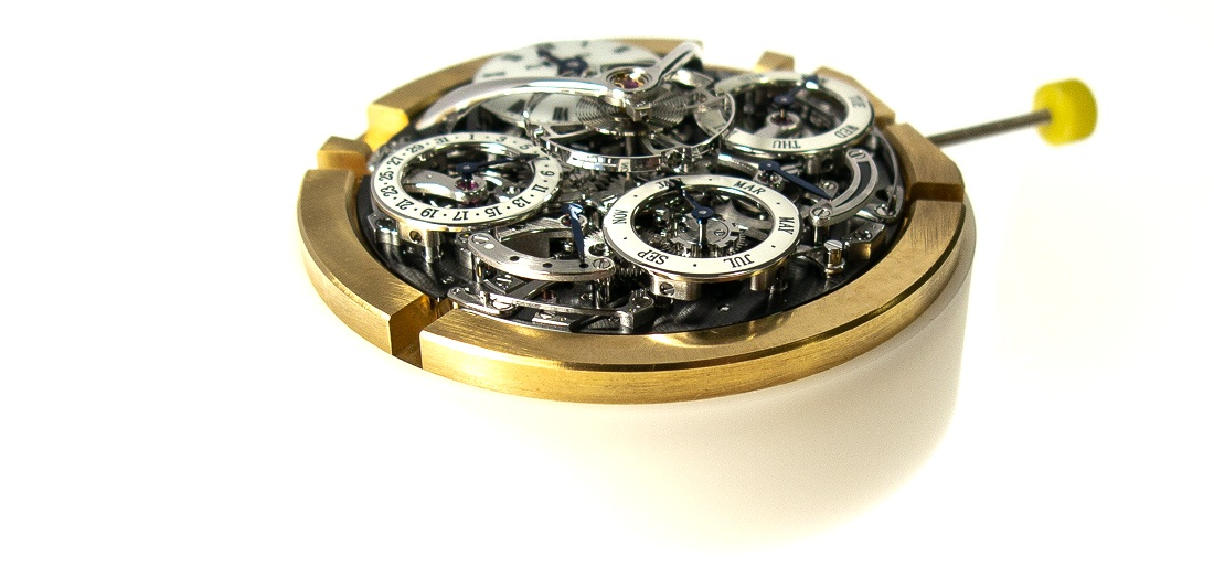 The movement sitting in a brass movement ring and placed on to a nylon support for manipulation, allowing the movement to be turned over to allow access to both sides during assembly.
