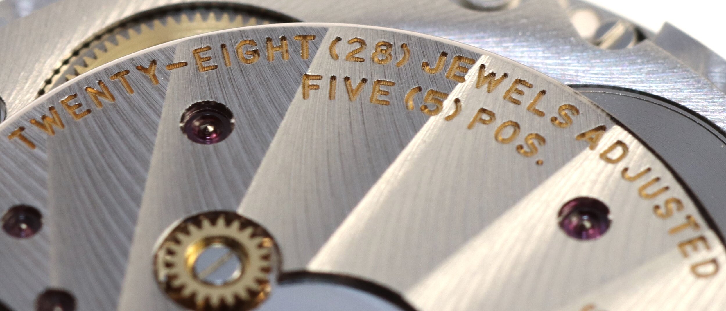 The top surface of the bridges are finished with Geneva stripes, the lower with a snailing effect. The engraving is executed at the same time as the bridge is machined.