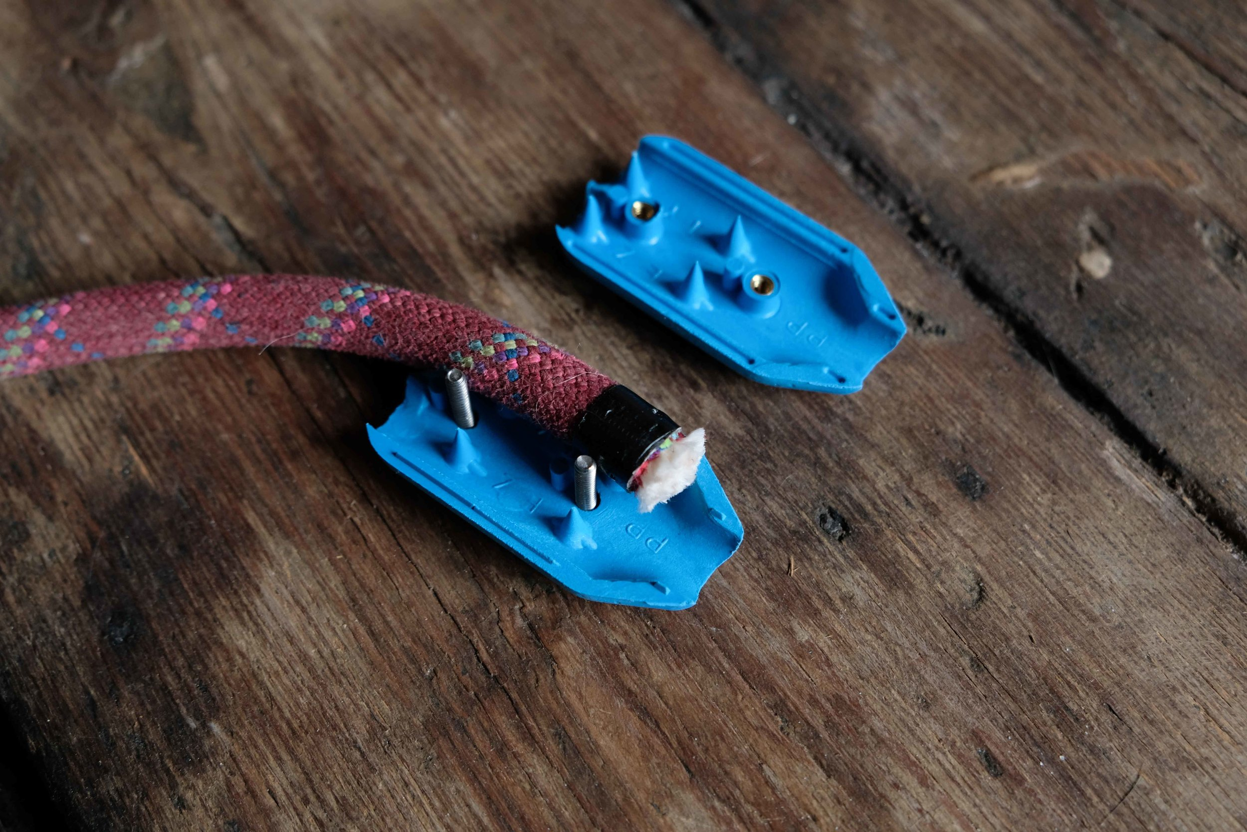 First, tape off each end of the rope with some electrical tape to prevent unravelling. Open each clamp, and press the end of the rope in place, around the screws. For an in depth how-to, watch  this video.