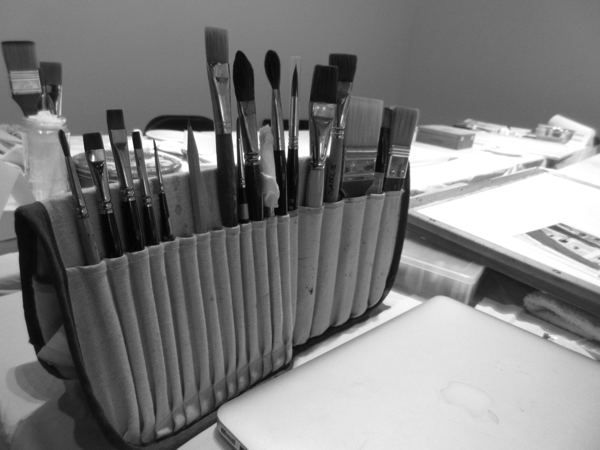 A student prepare's their station with their personal art supplies.