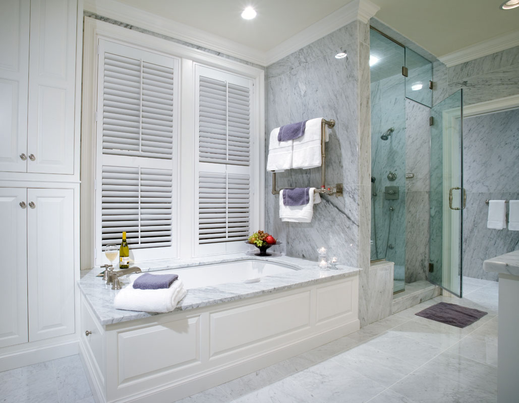 Grand Baths - As a way to make a statement these homeowners used marble as a textural element for all areas except the white painted custom cabinetry. The result was beautiful bathroom with classic style.