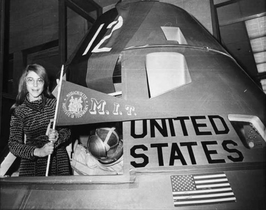 Margaret Hamilton poses with an MIT pennant inside an Apollo lunar capsule model. (Credit: MIT Museum)