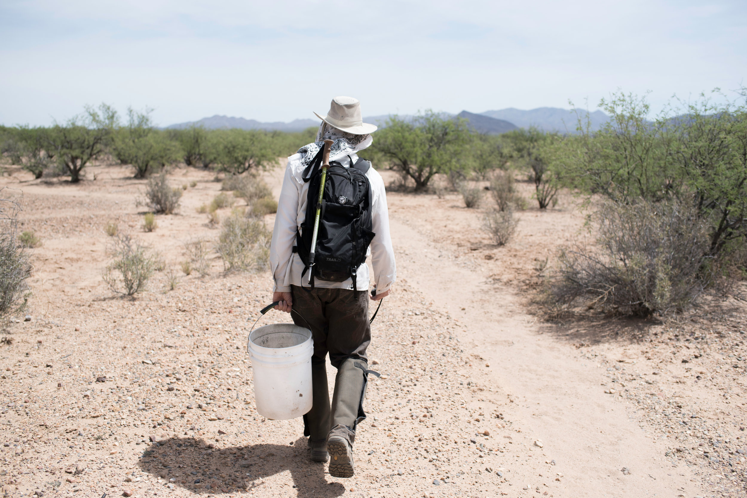 One of Alvaro's volunteers carries water for miles towards a new grave site .jpg