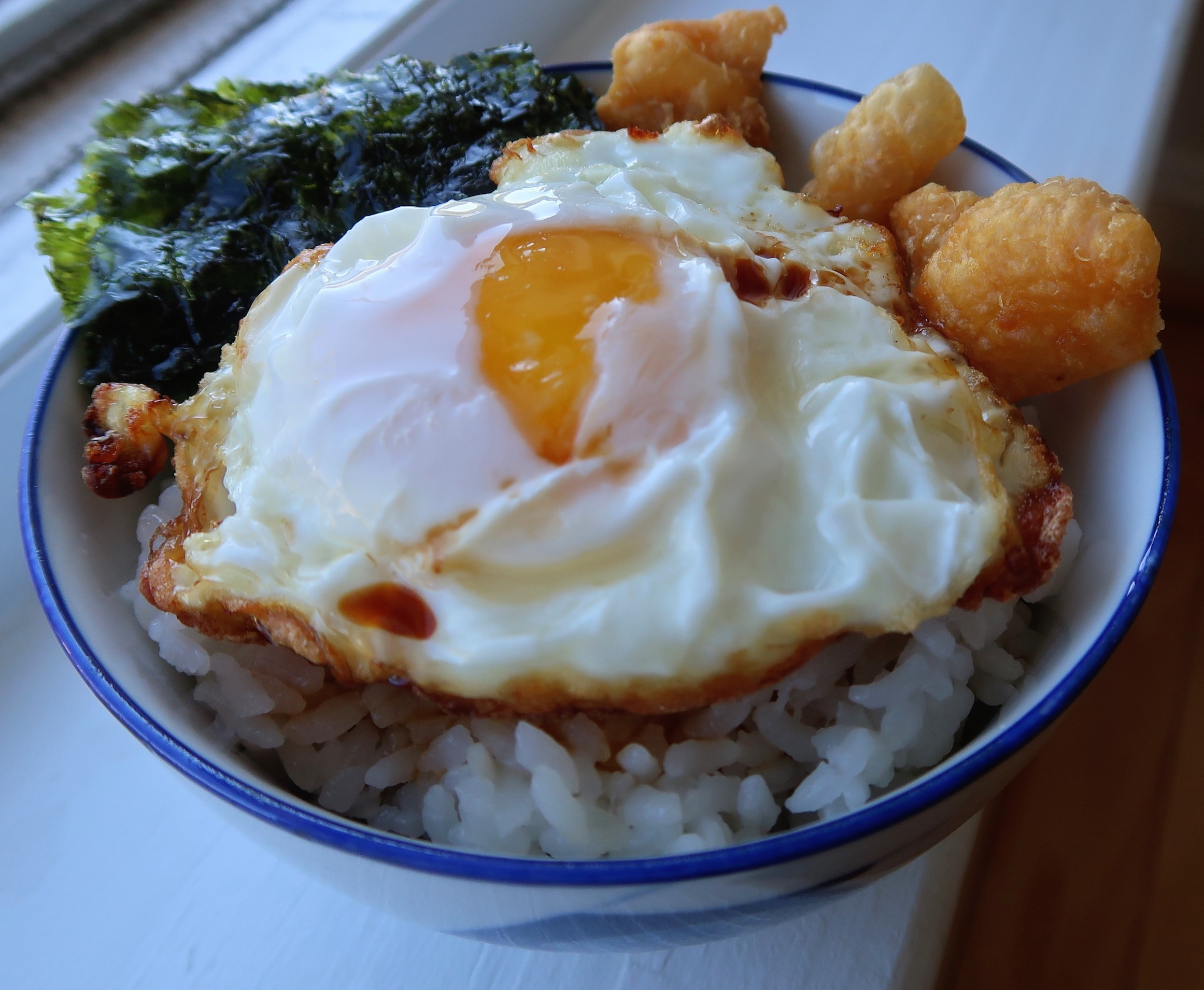 Rice drizzled with chicken drippings, Haku Smoked Shoyu before being topped with fried egg, fried chicken skin, and roasted seaweed with sesame oil