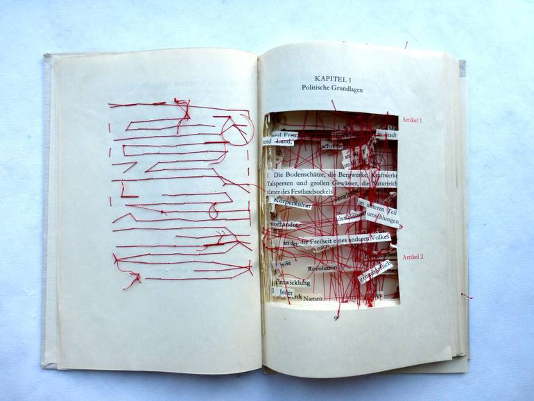 Ines Seidel,  Out of the Constitution  , ( date unknown) Fabric, Paper and Book, all words and phrases that were dead or lies have been cut out. the words that still had meaning were held in place by red thread, 14.6 H x 16.5 W x 1.6 in