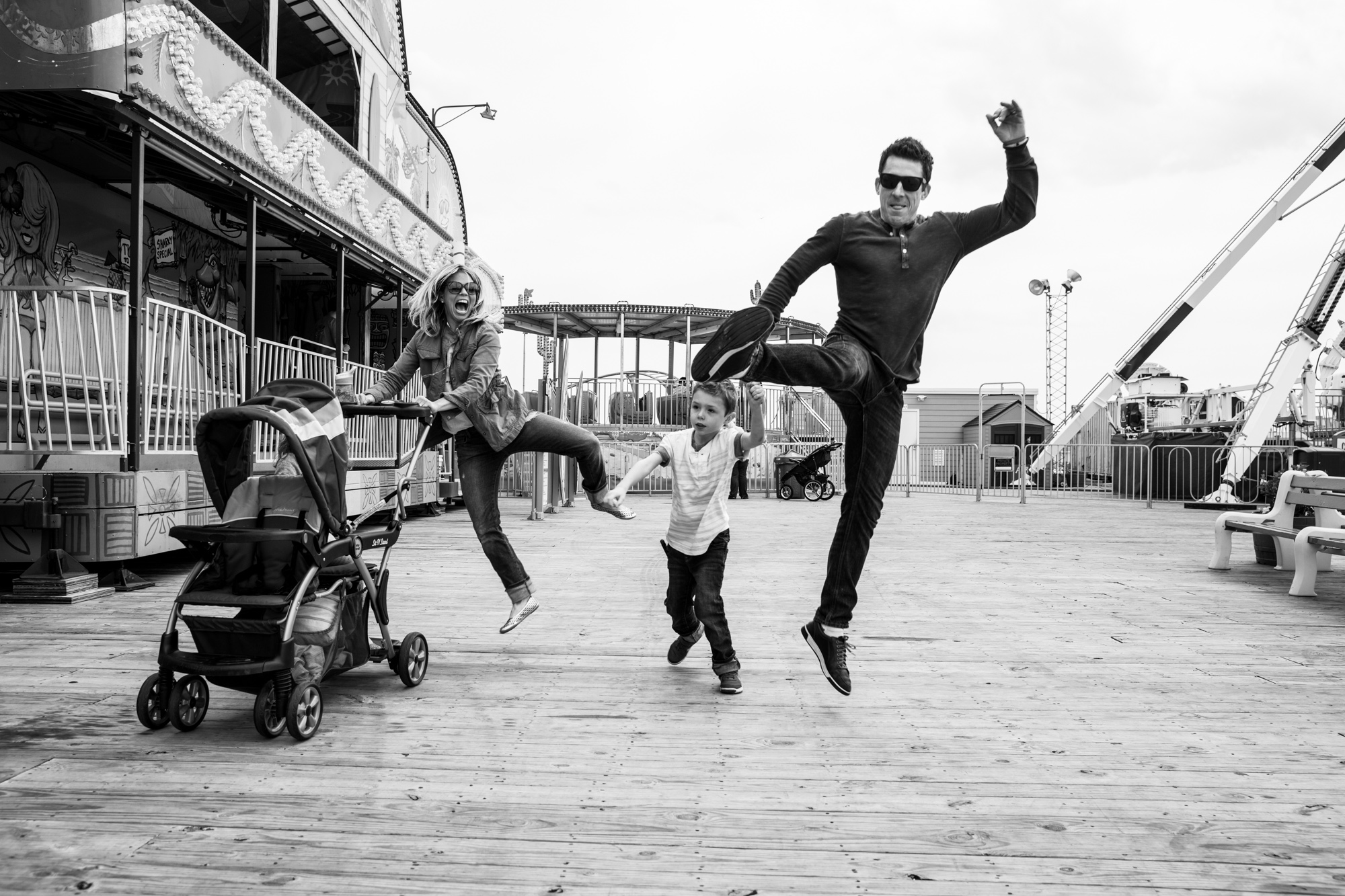 Family does bell kicks while pushing stroller at the boardwalk