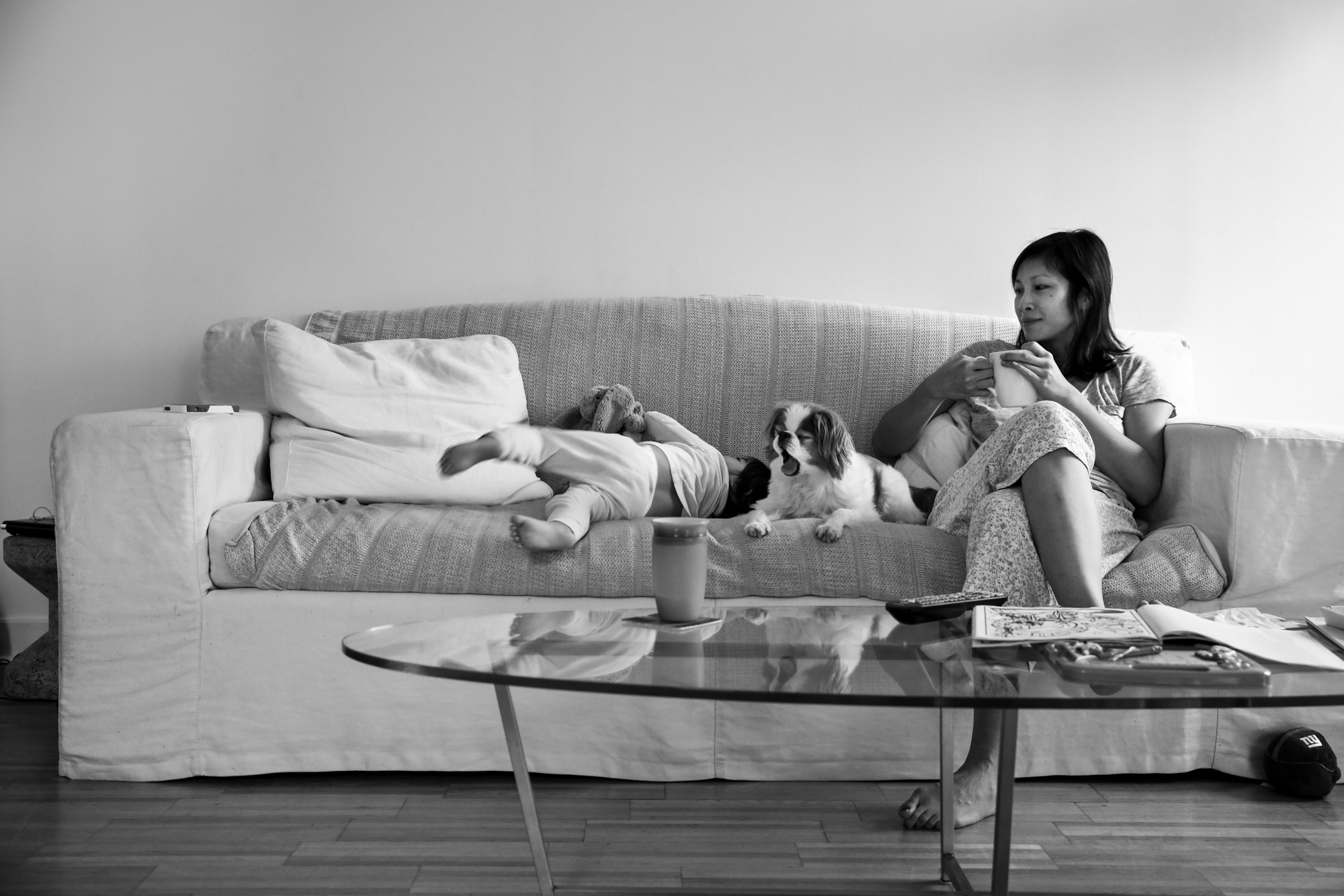 Woman with coffee sits on a couch with a girl and dog yawning