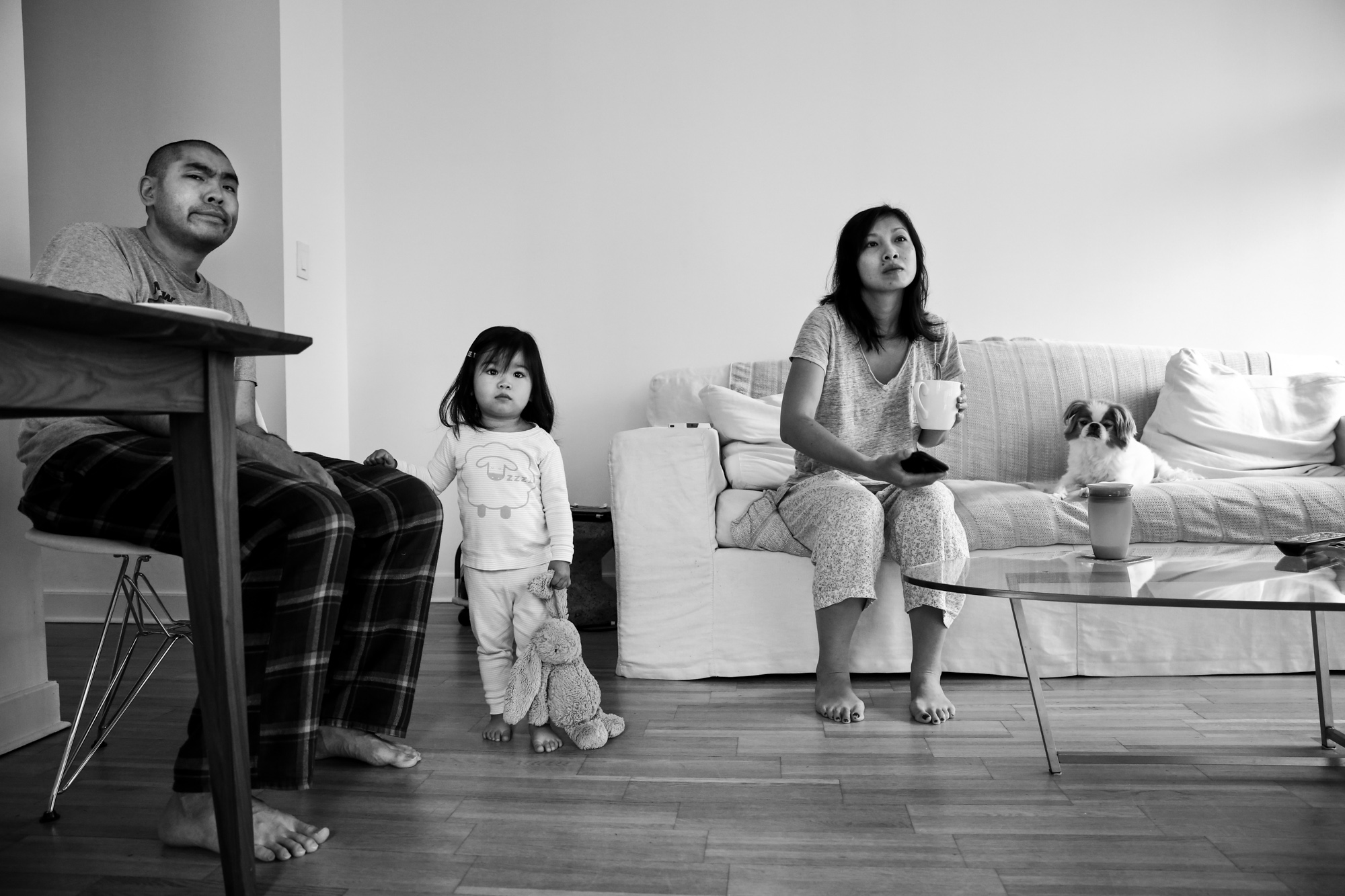 Man sits at table while child stands with stuffed bunny and woman sits on couch with dog