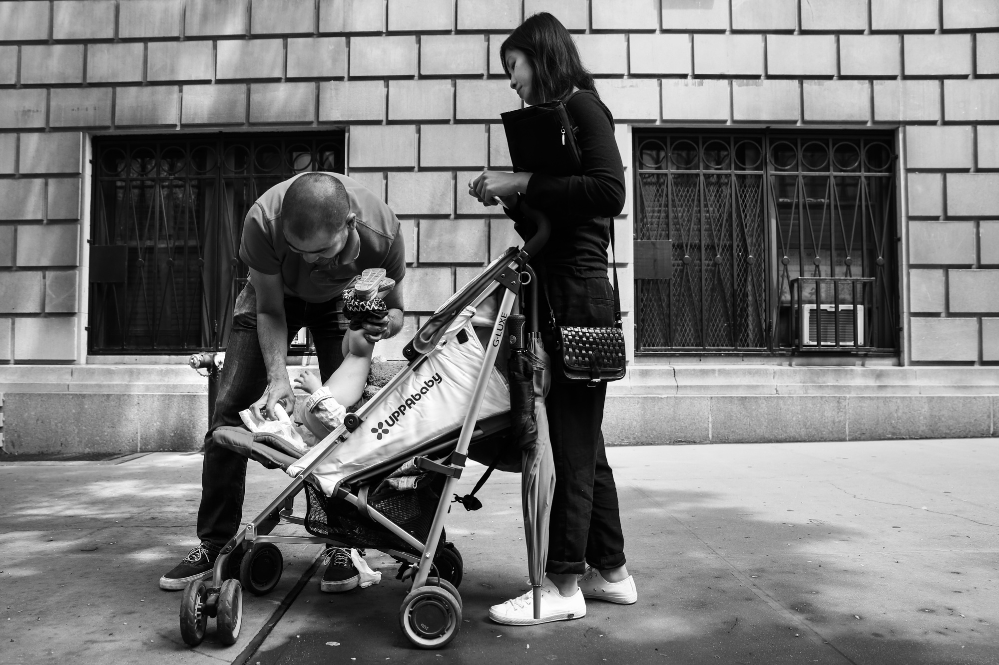 Man changes diaper on the sidewalk in a stroller