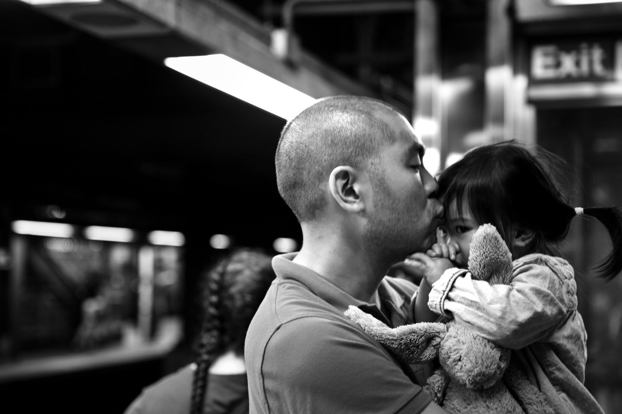Man kisses girl on her forehead while she holds a stuffed bunny and sucks her thumb