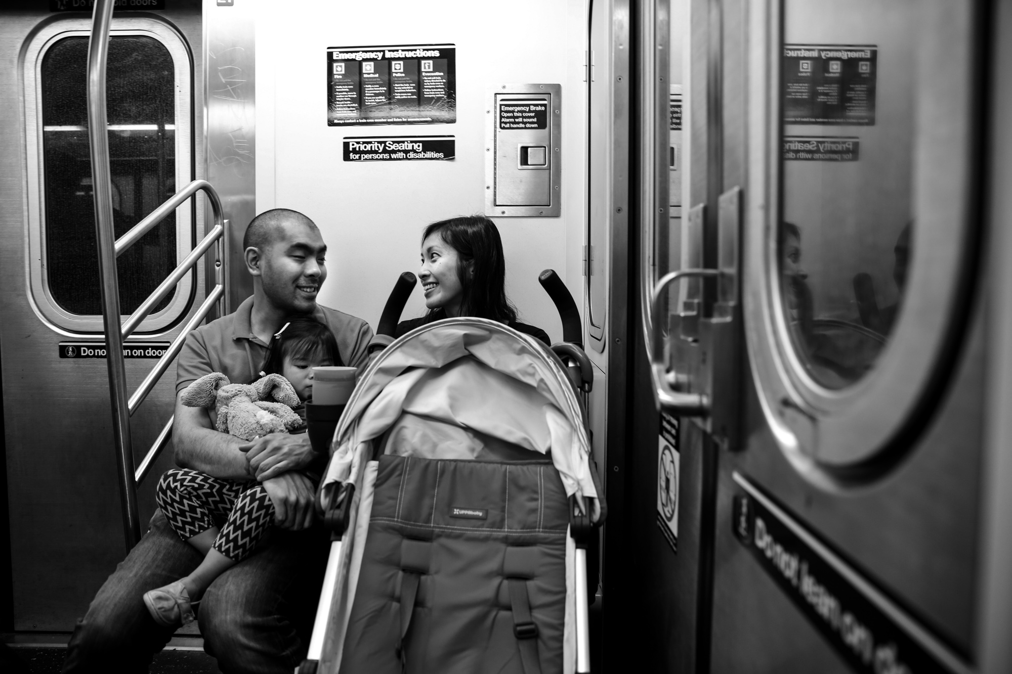 Man, woman and child ride the subway with their stroller