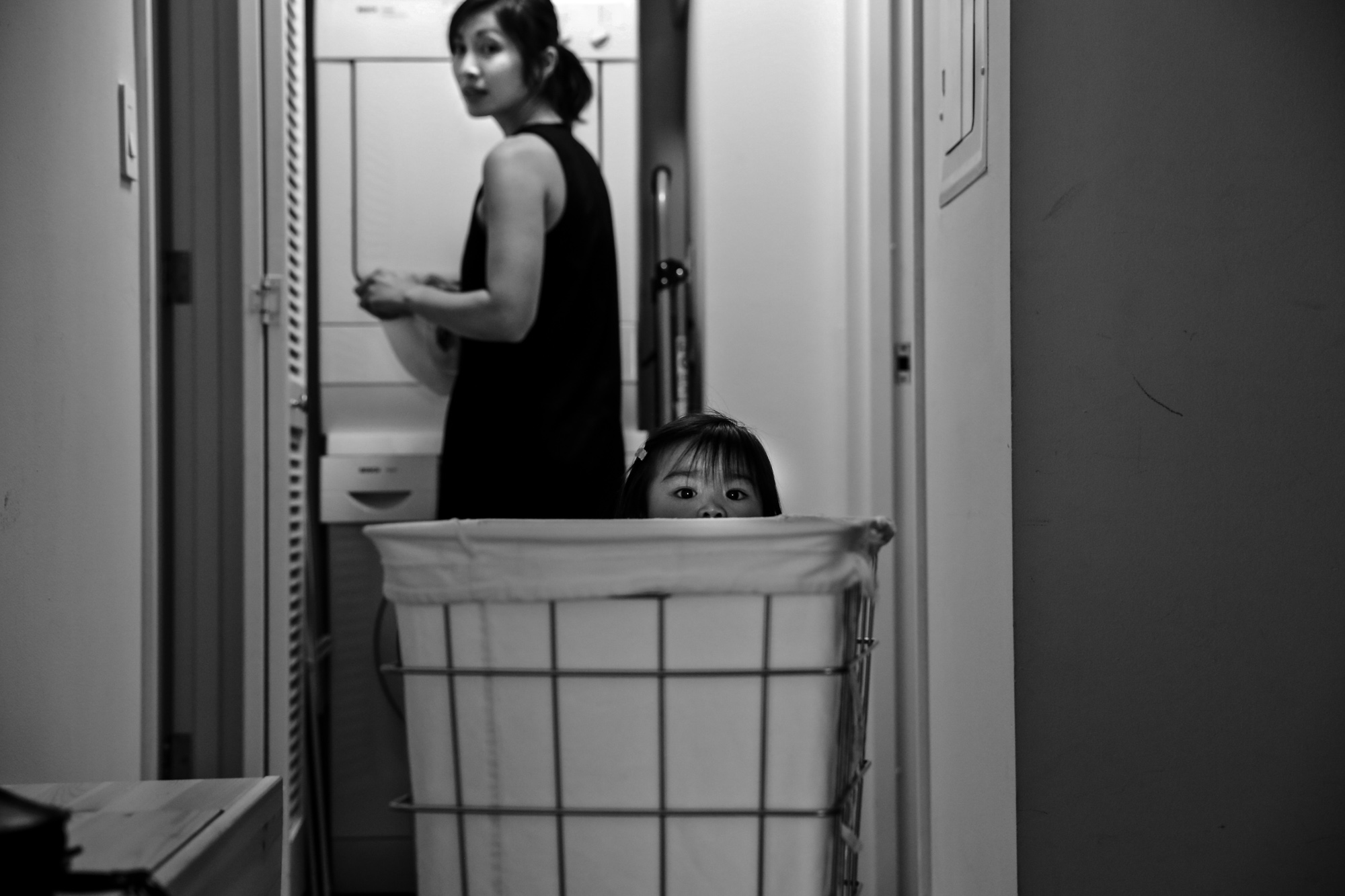 Girl peeks out behind laundry basket while woman looks