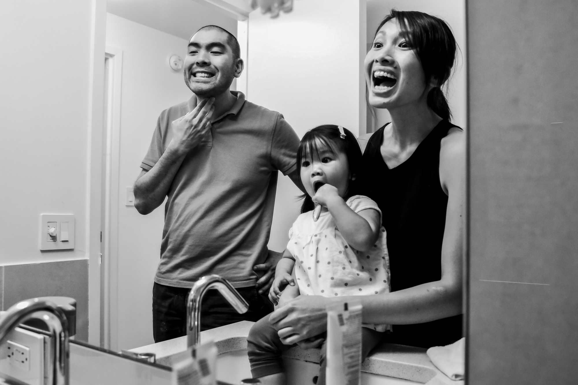 Man and woman make silly faces in the mirror while girl brushes teeth