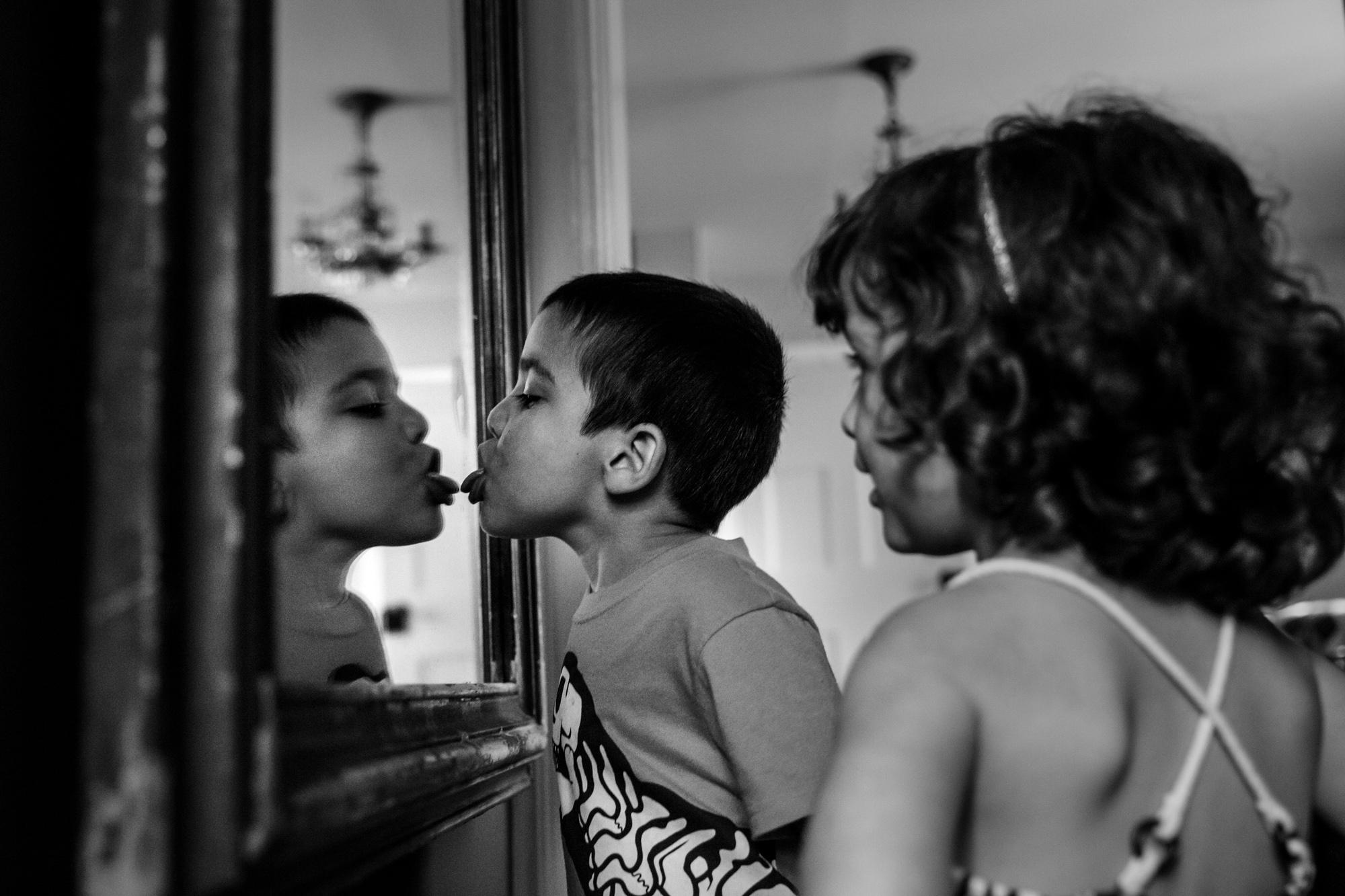 Boy licks mirror while girl watches