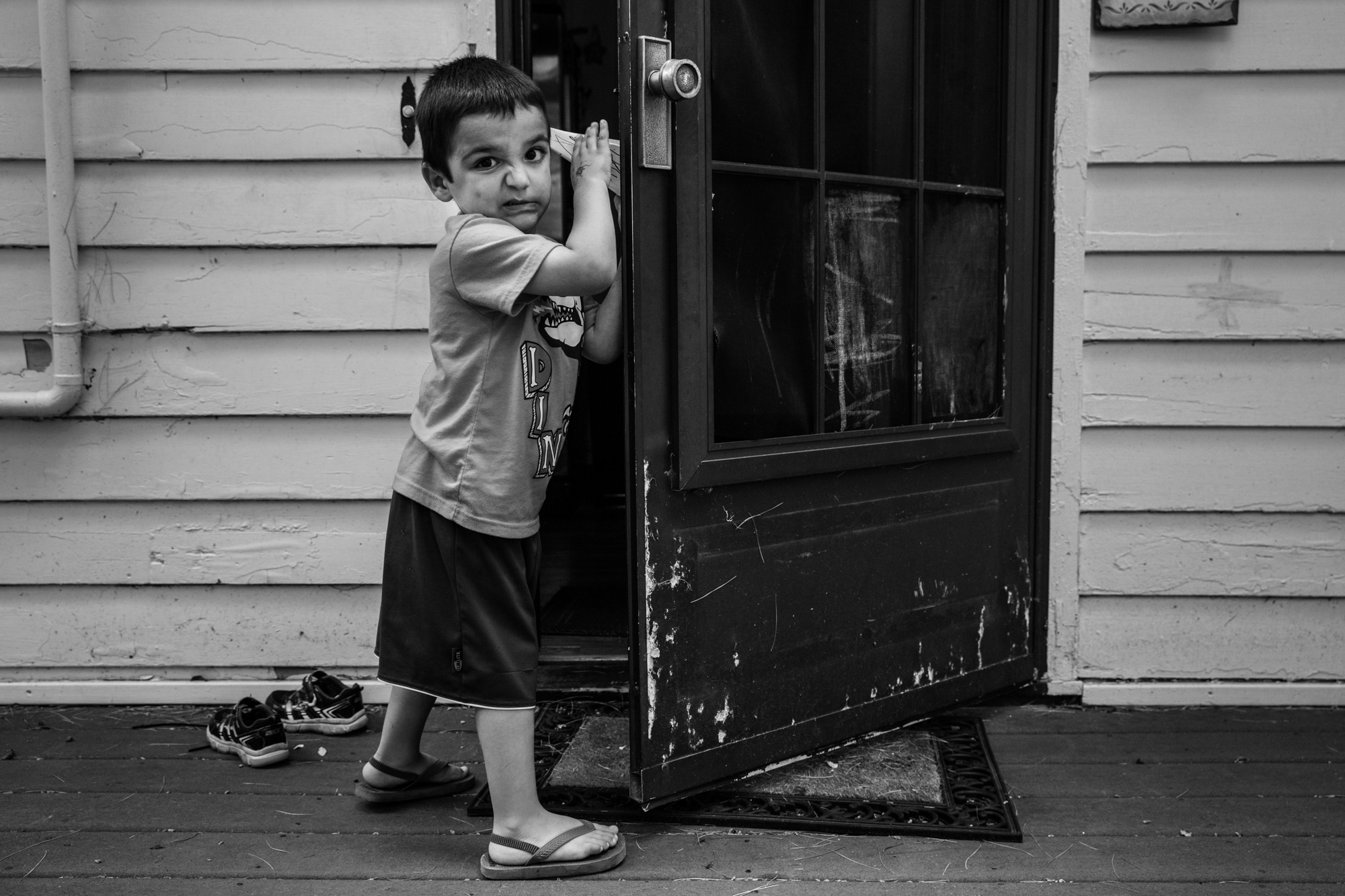 Boy grimaces while holding open a door