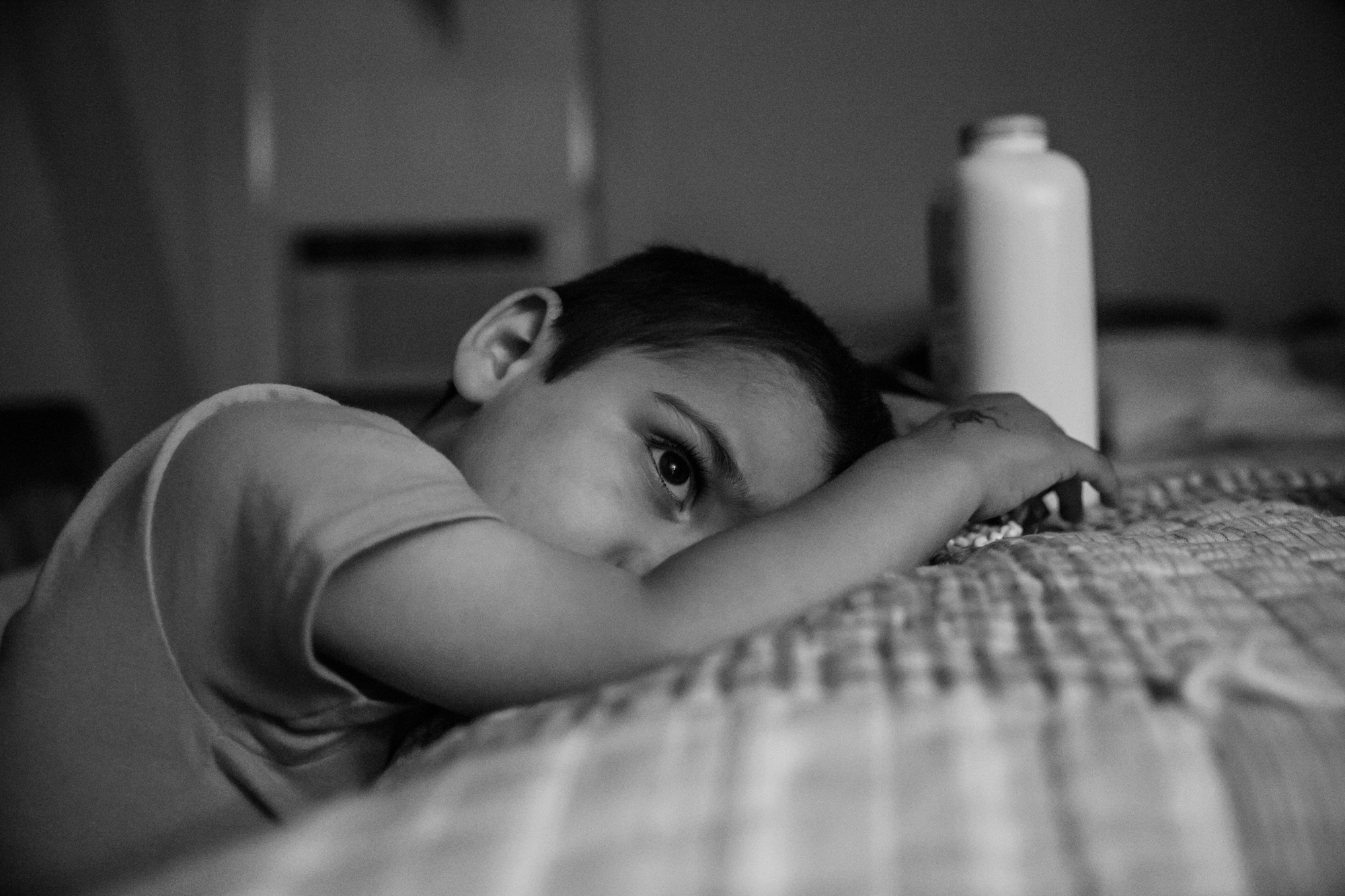 Tired boy leans on bed with a white bottle