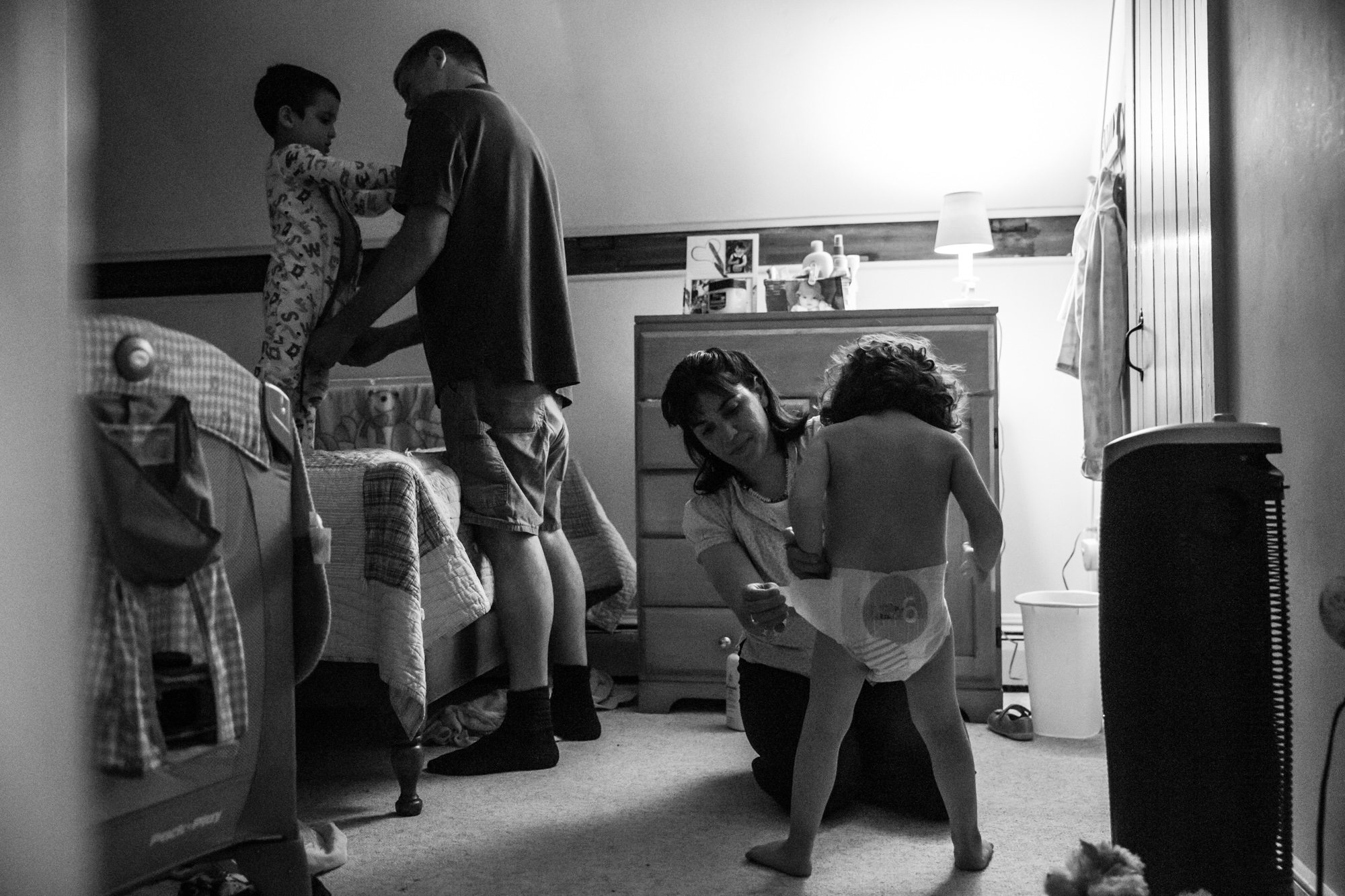 Man dresses boy in pajamas while woman puts diaper on girl