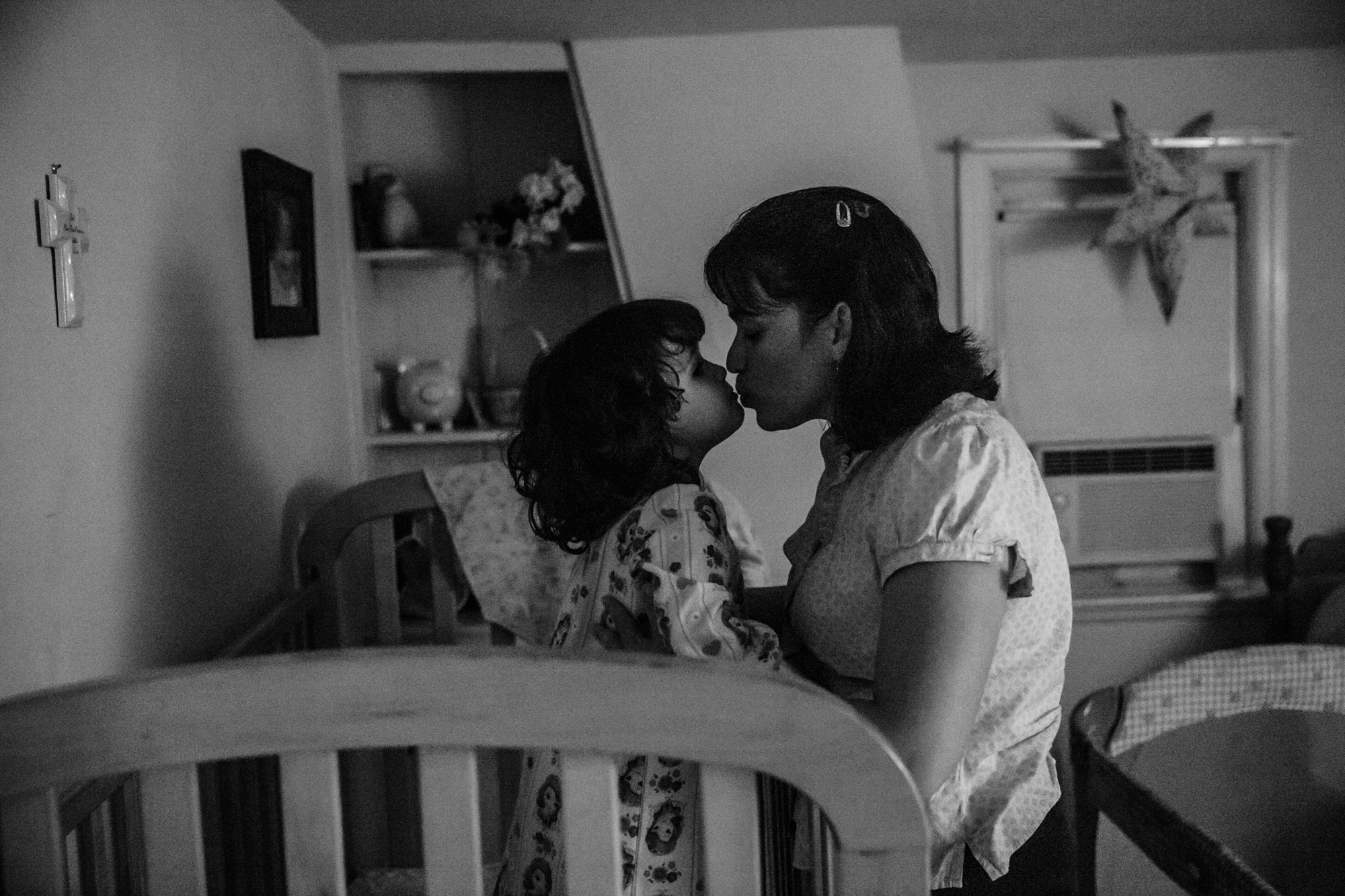 Woman kisses girl on lips while standing in crib