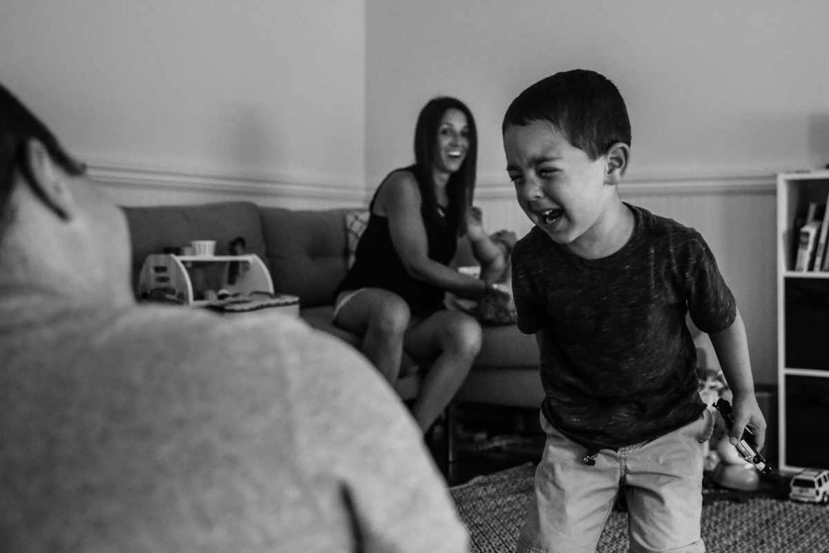 Boy holding a toy car cries while mom is surprised in the background