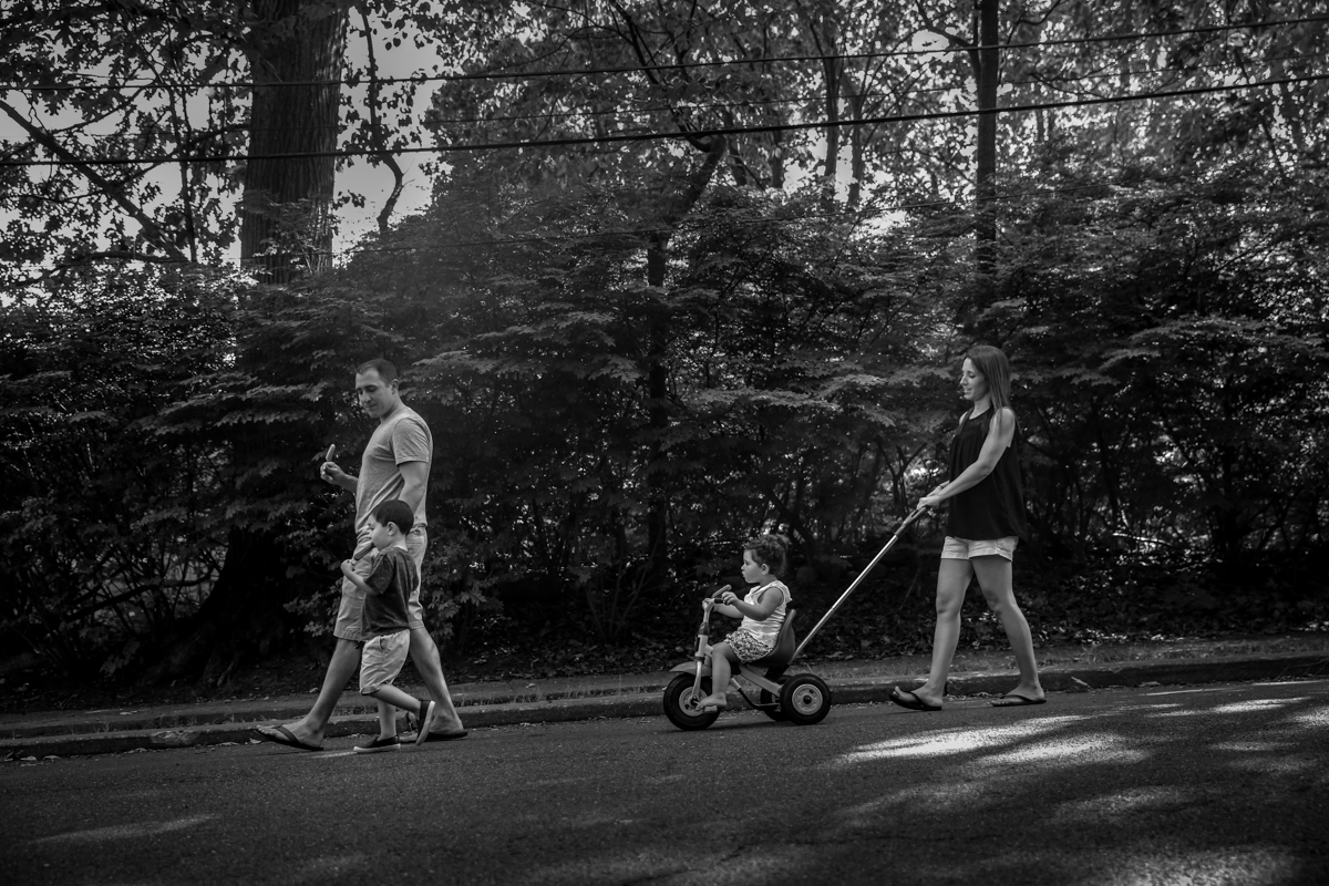 A family of four walk down a street while eating ice pops